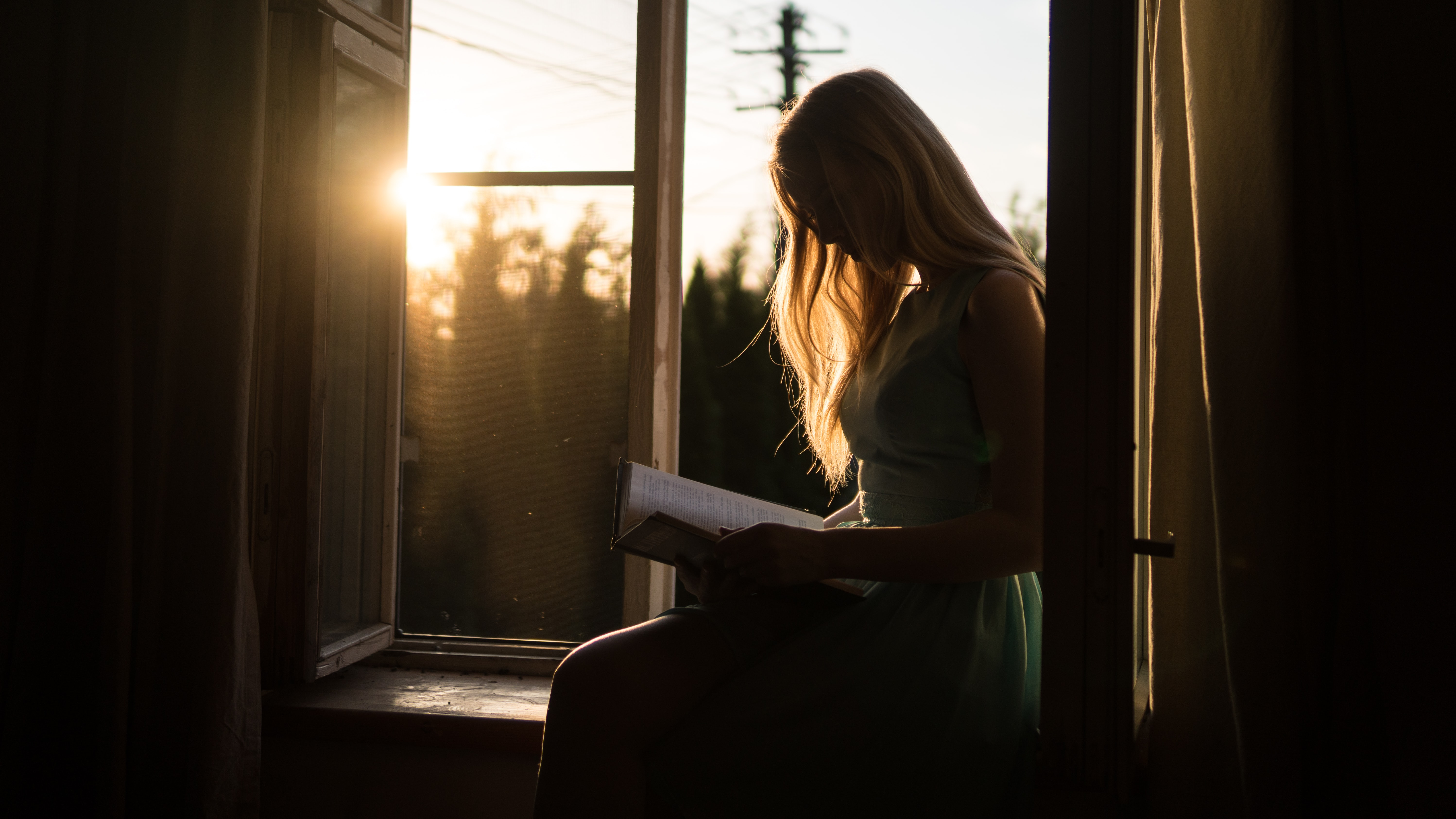woman reading book while sitting at window