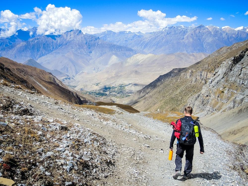 man carrying backpack walking on mountain at daytime