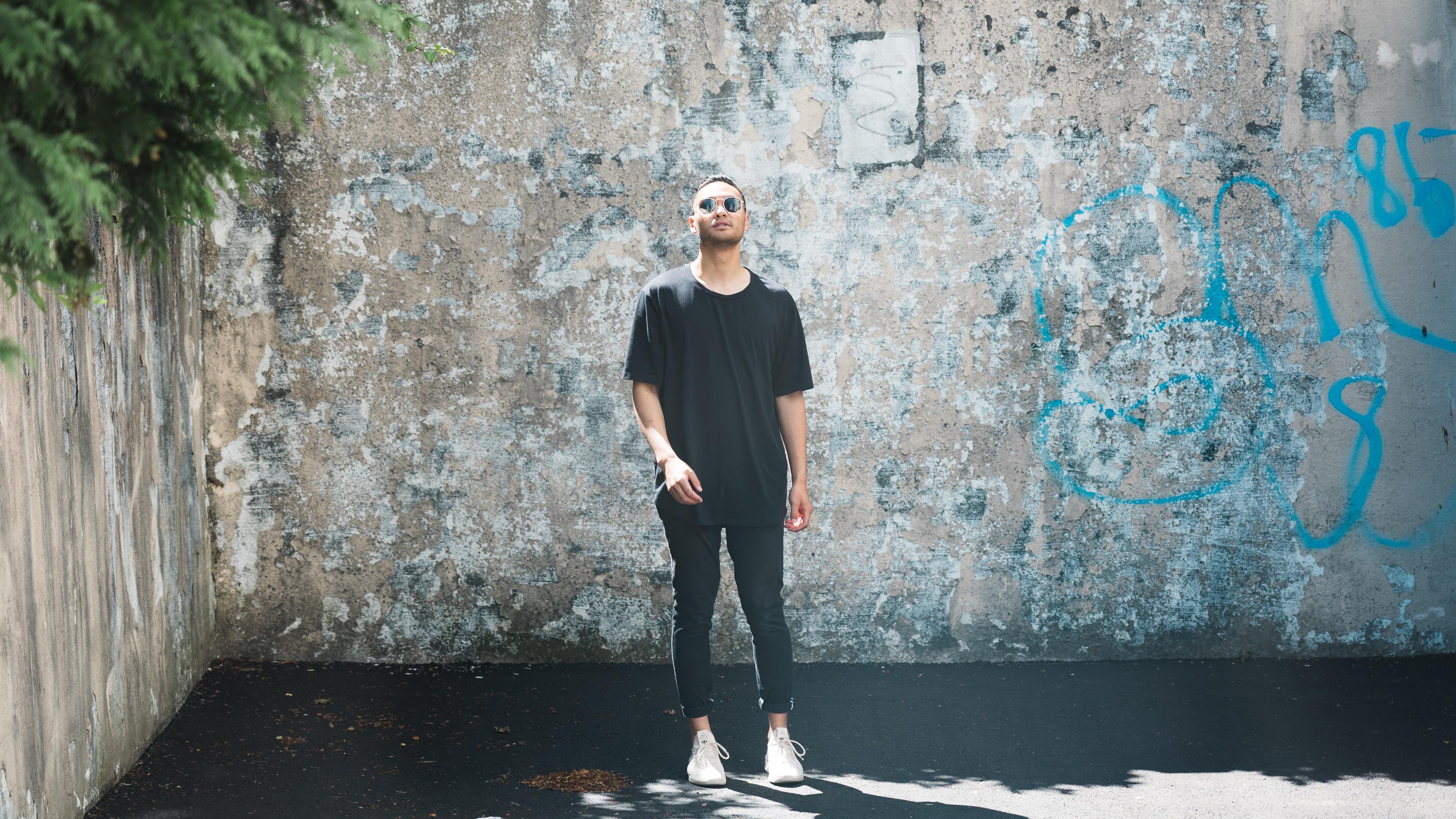 man standing beside walls