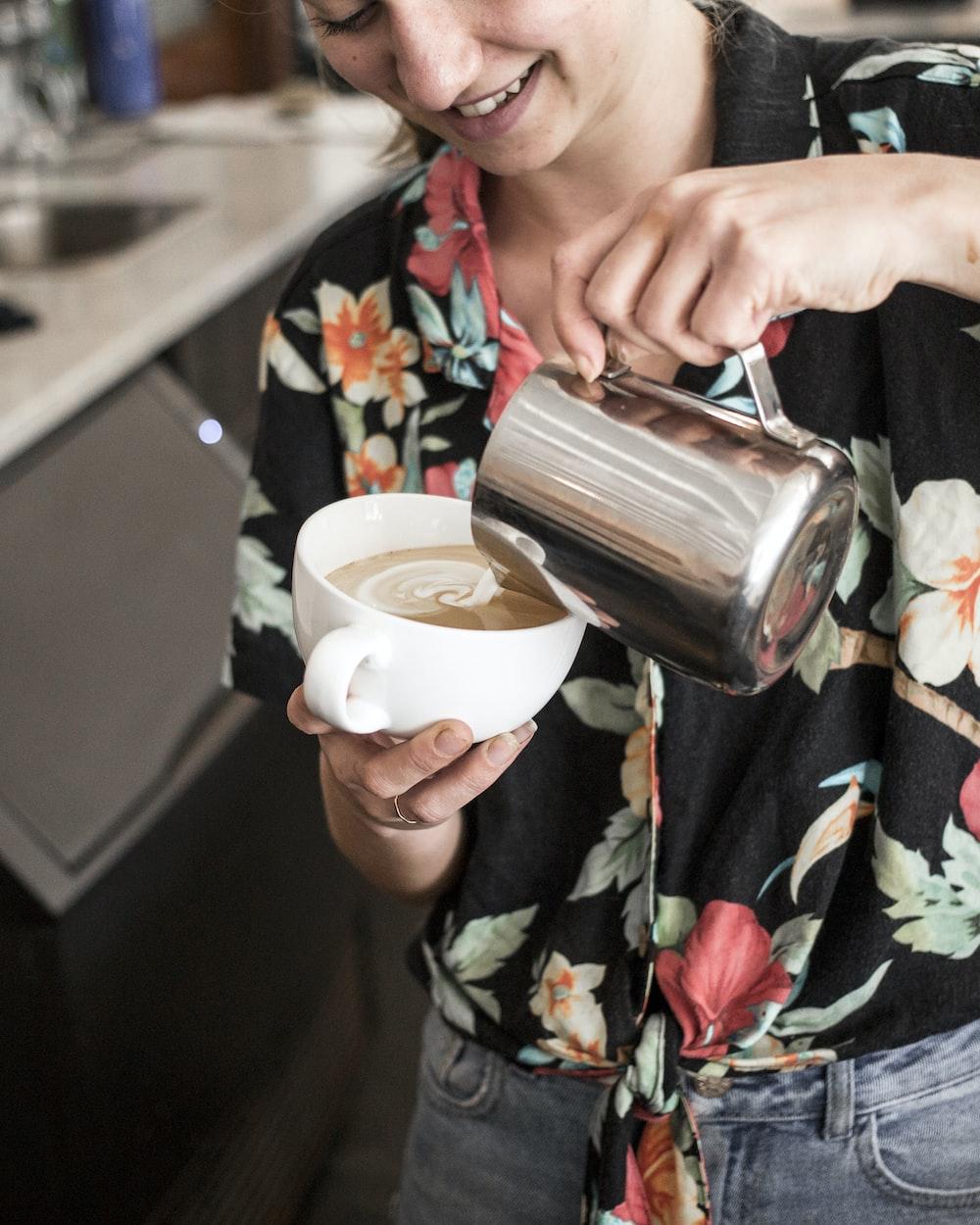 woman pouring coffee on white mug