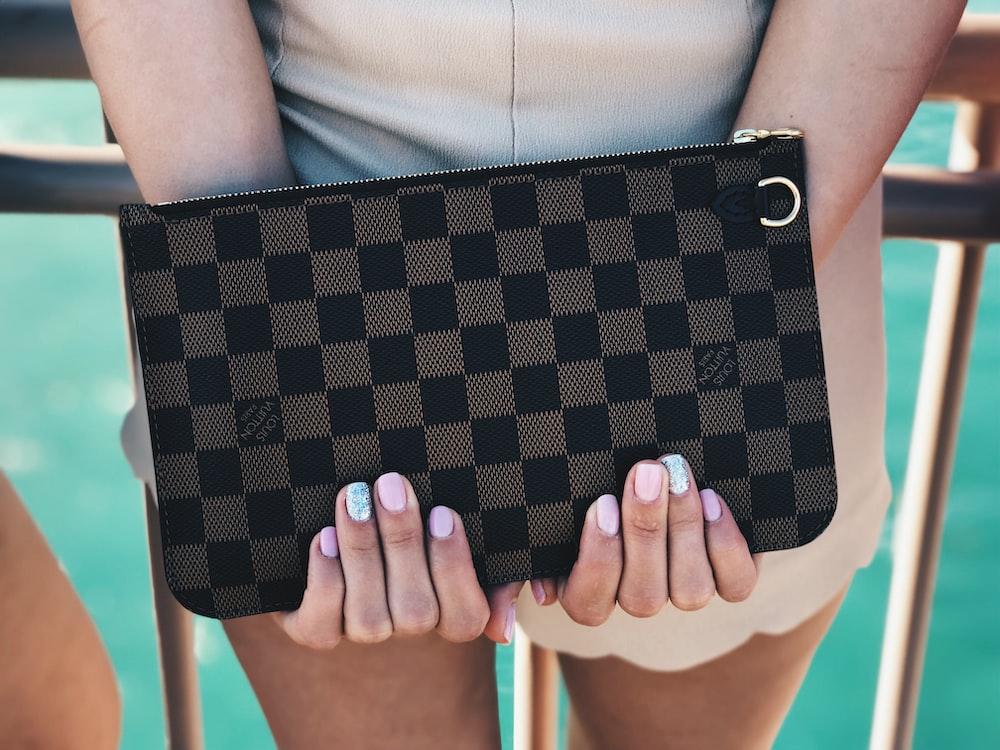 person holding Damier Graphite Louis Vuitton bag