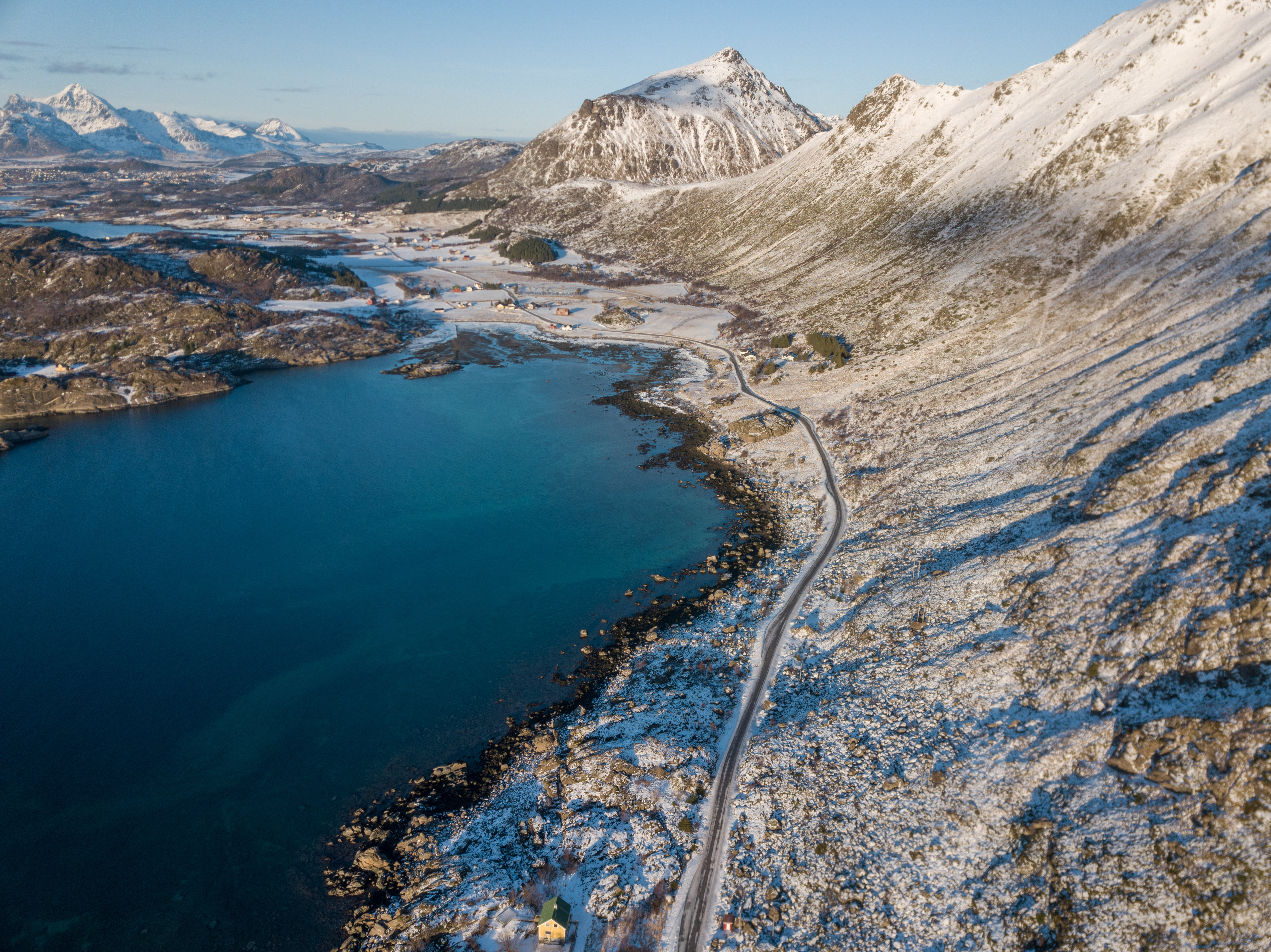 birds-eye view of snow-covered mountain and body of water