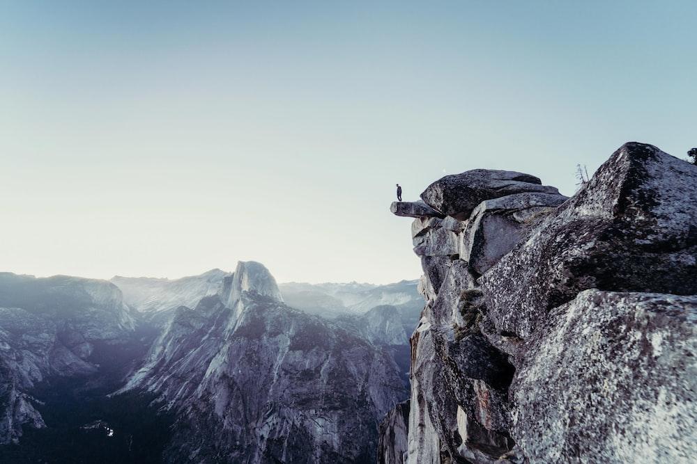 persona sul piglio di un burrone tra montagne innevate