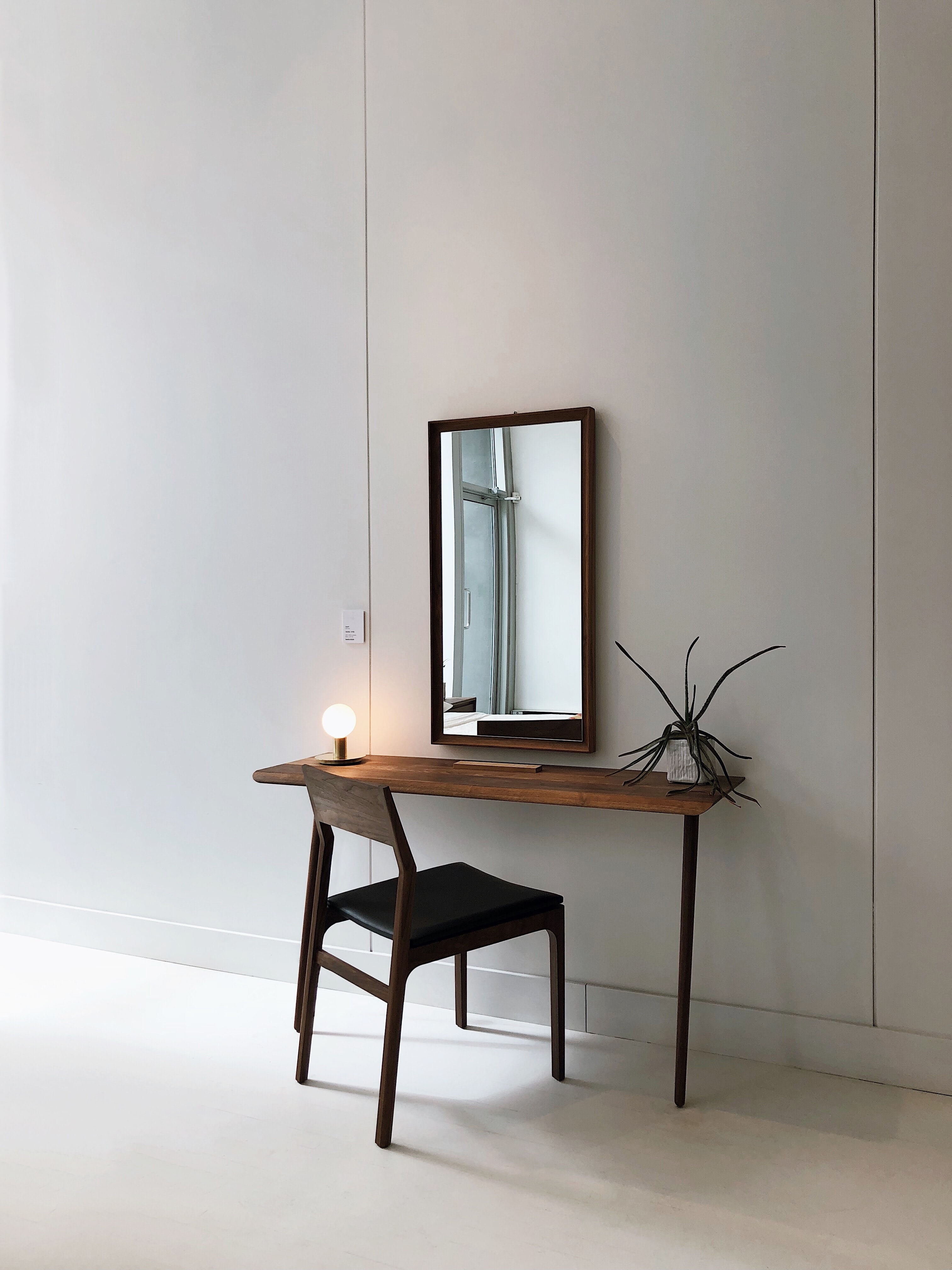 black leather chair with brown wooden frame in front of half table