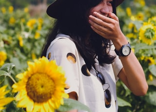 selective focus photography of woman between sunflowers