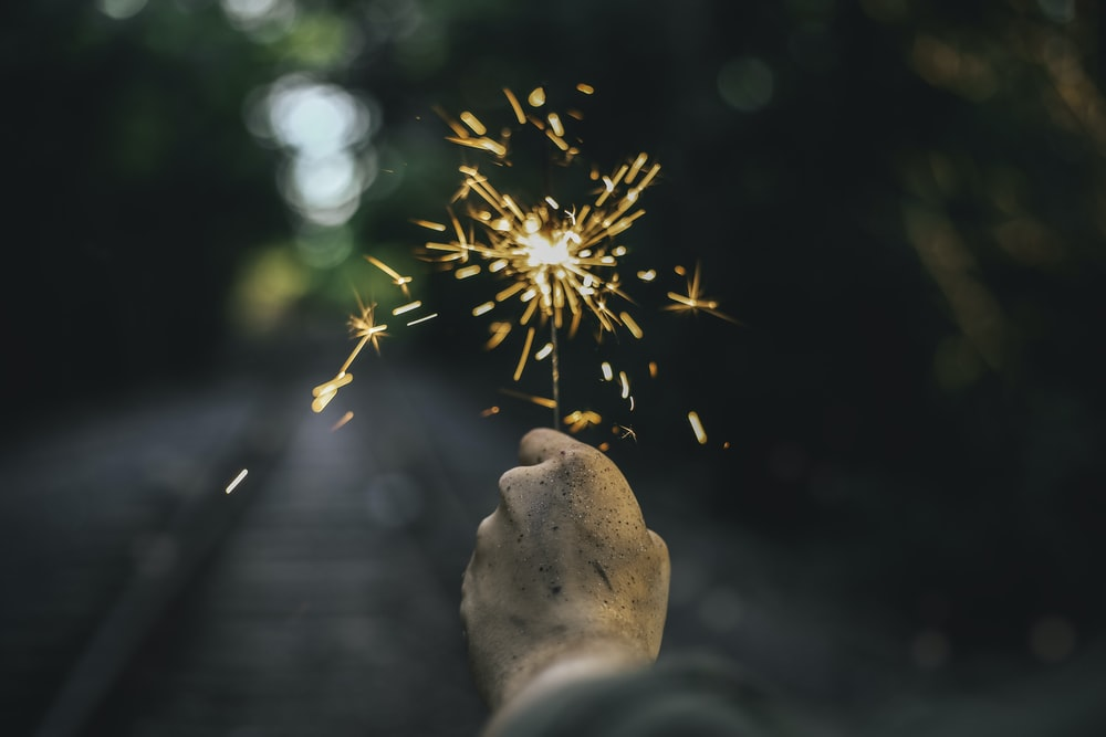 selective-focus photography of person holding sparkler