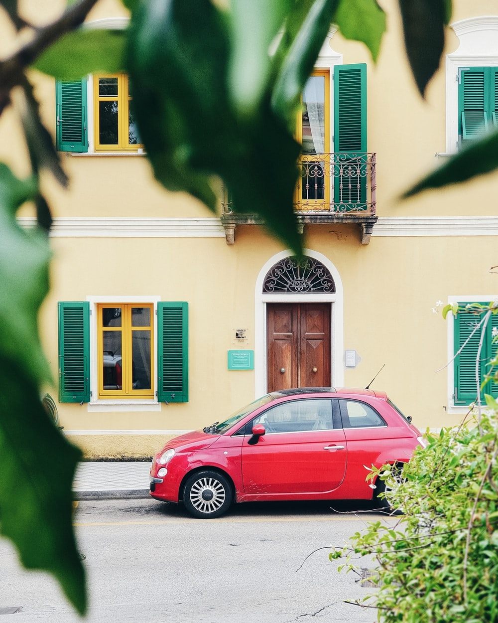 red FIAT 500 parked outside building