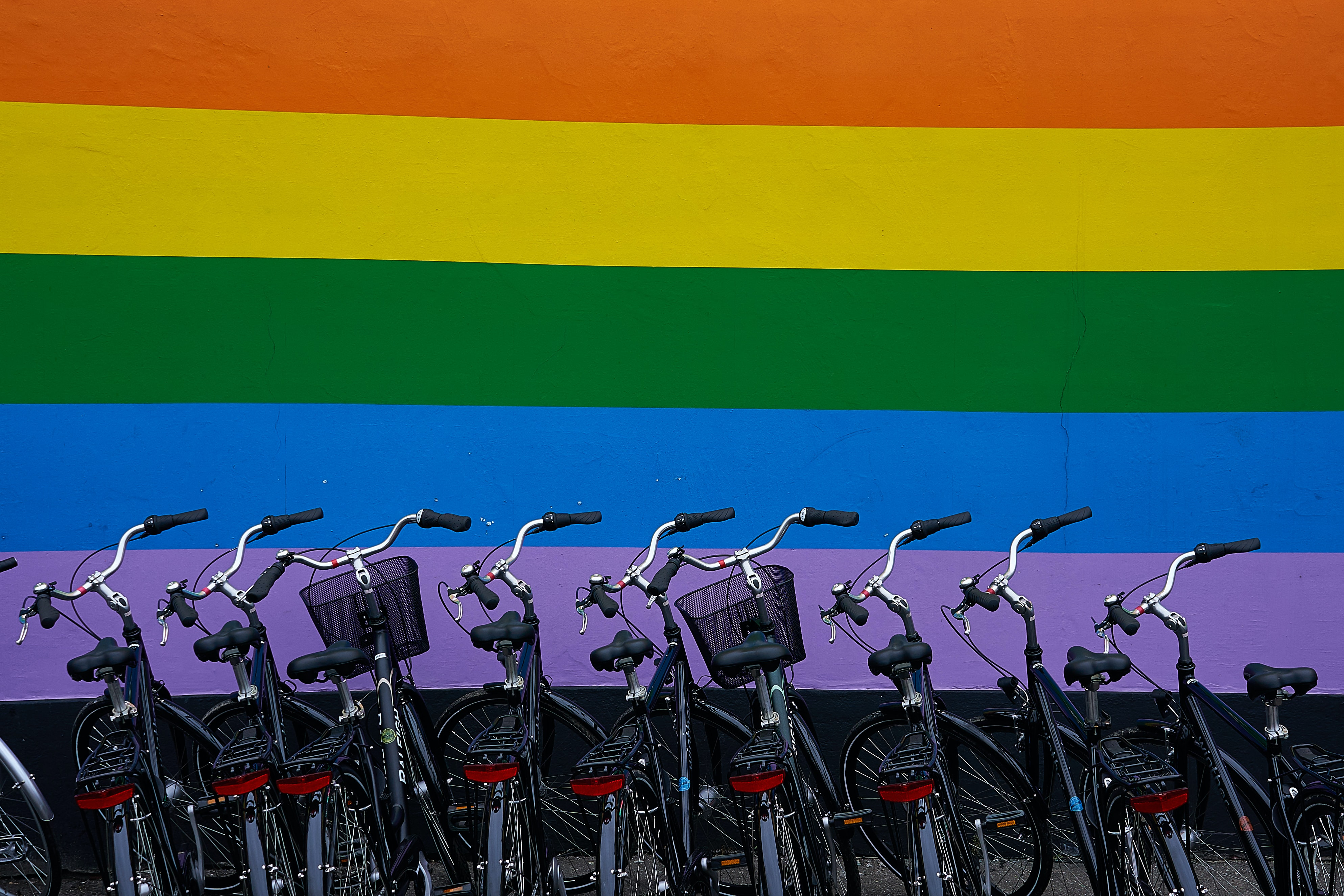 black commuter bikes parked near multicolored wall