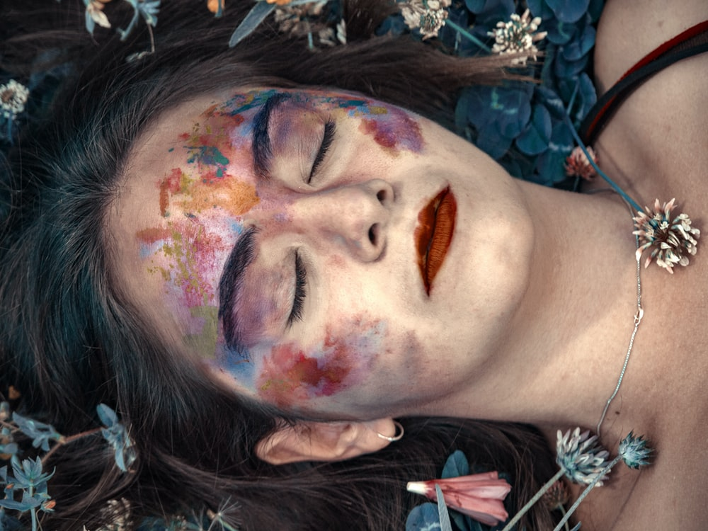 woman with multicolored makeup closed her eyes