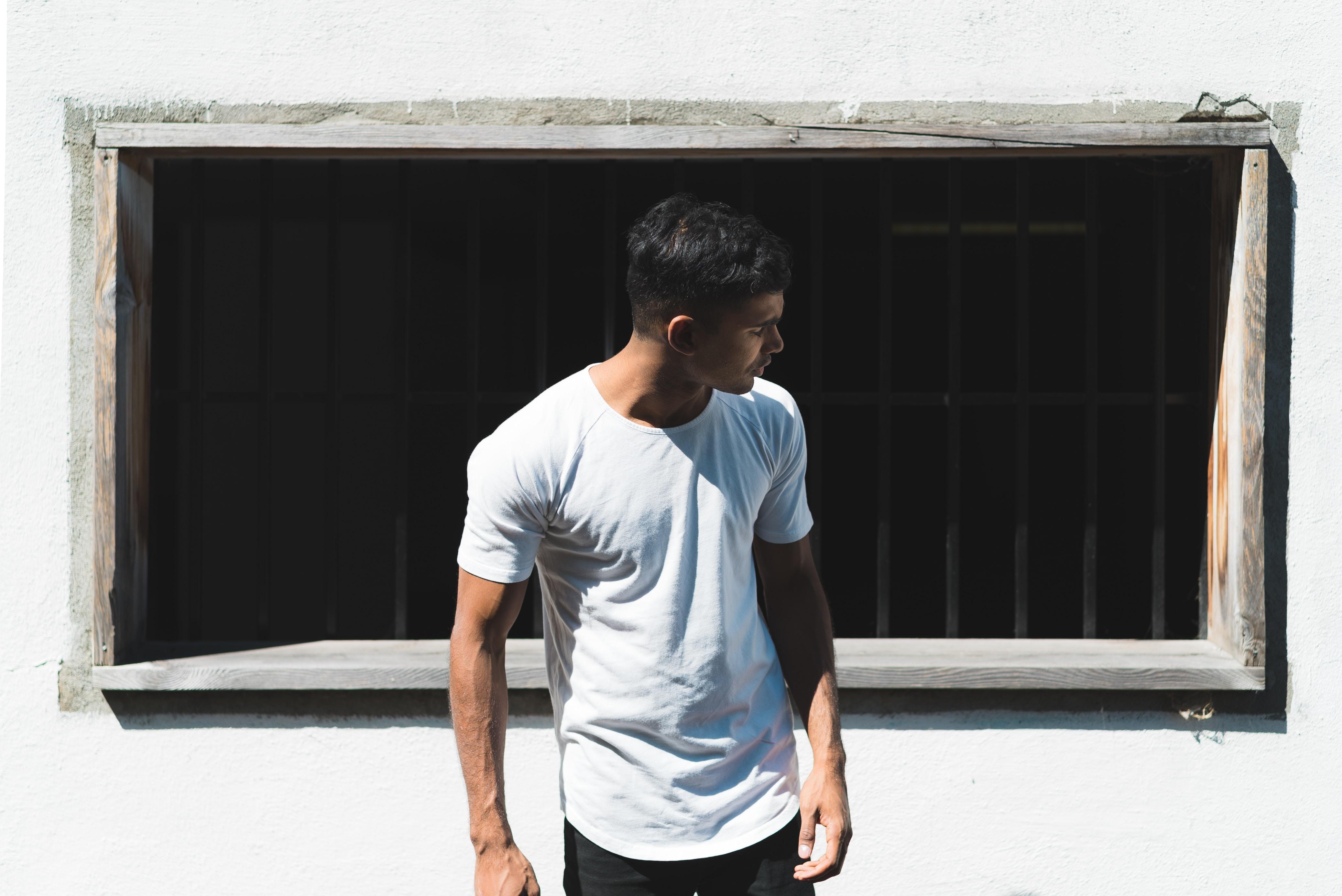 man standing near white wall
