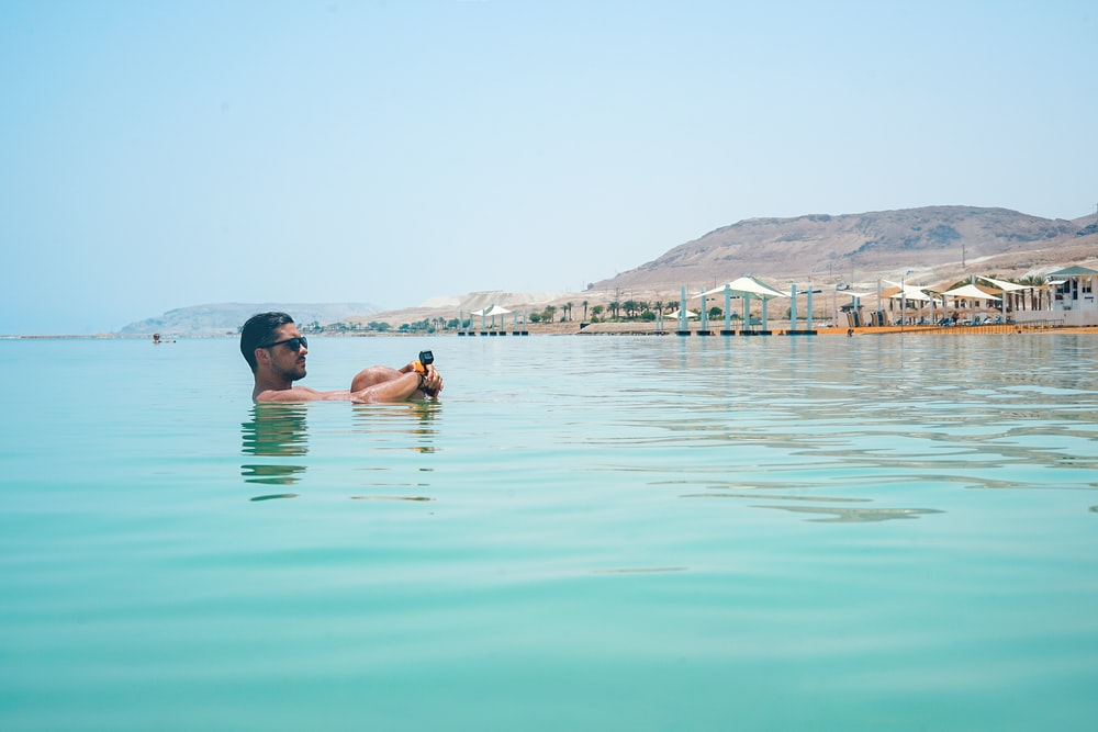 photo of man swimming in sea
