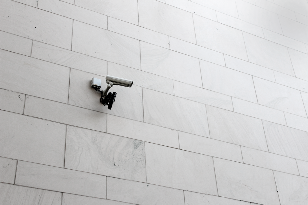 grey surveillance camera on wall
