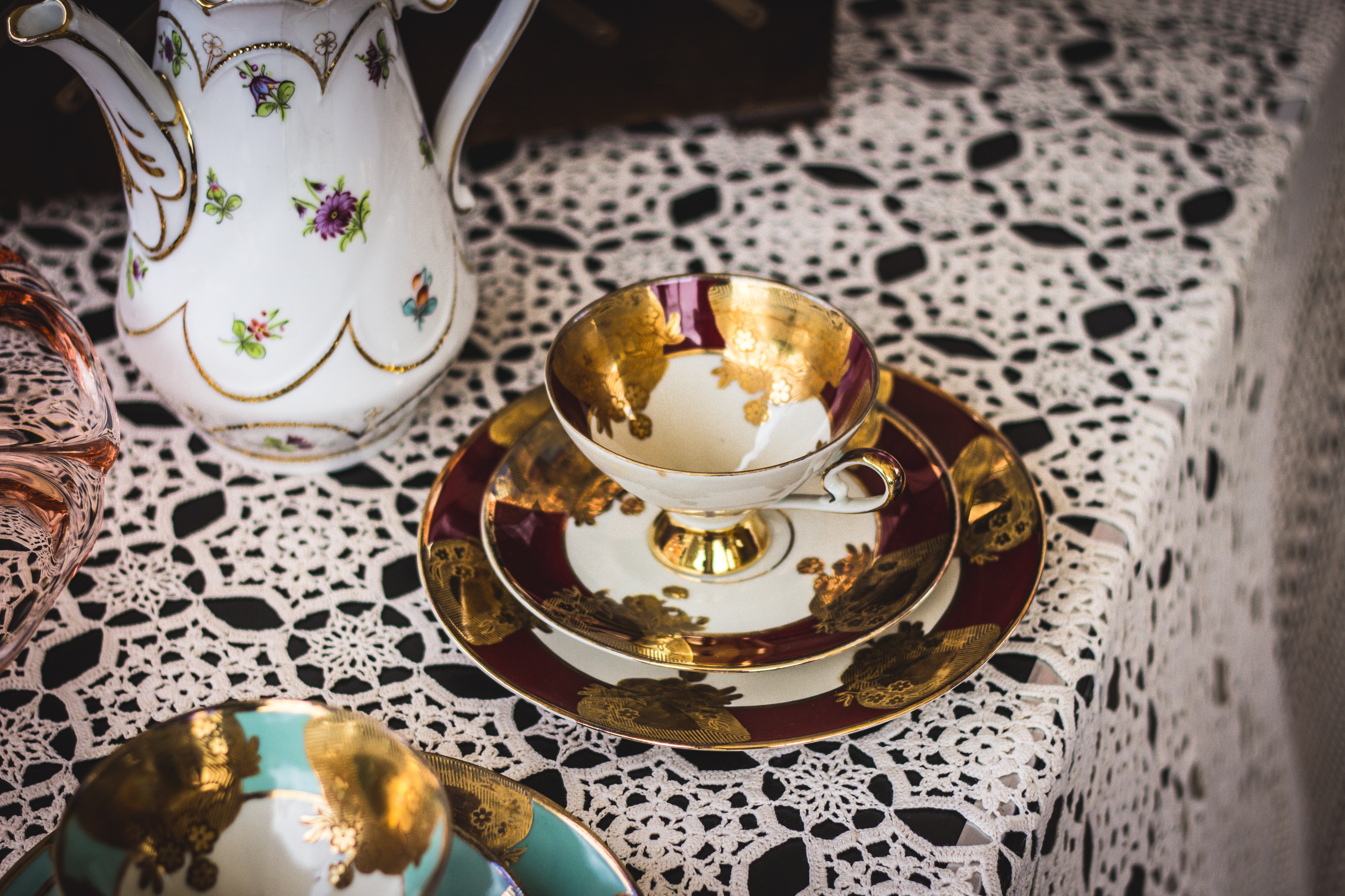 gold and white tea cup on saucer