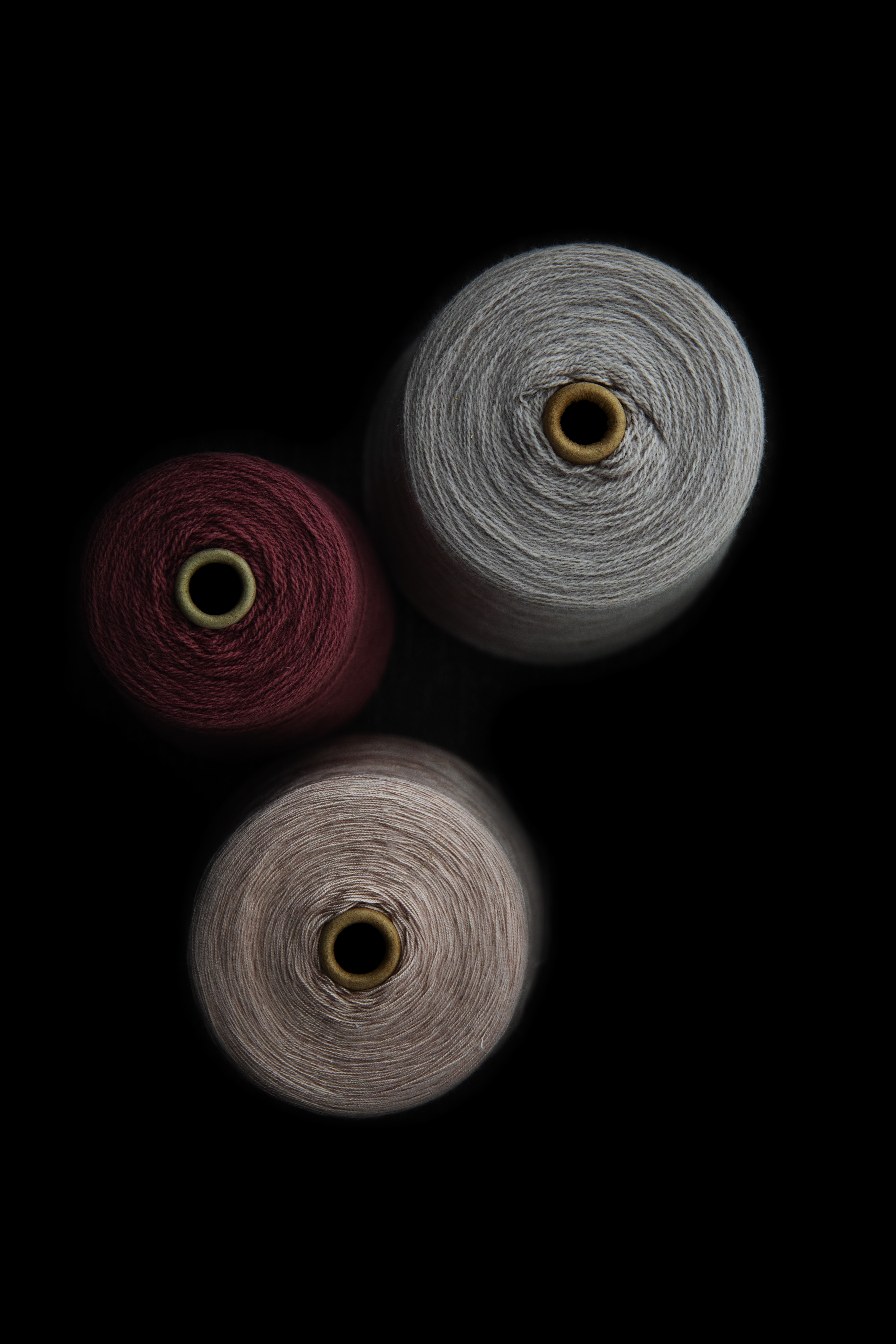 three assorted-color thread rolls