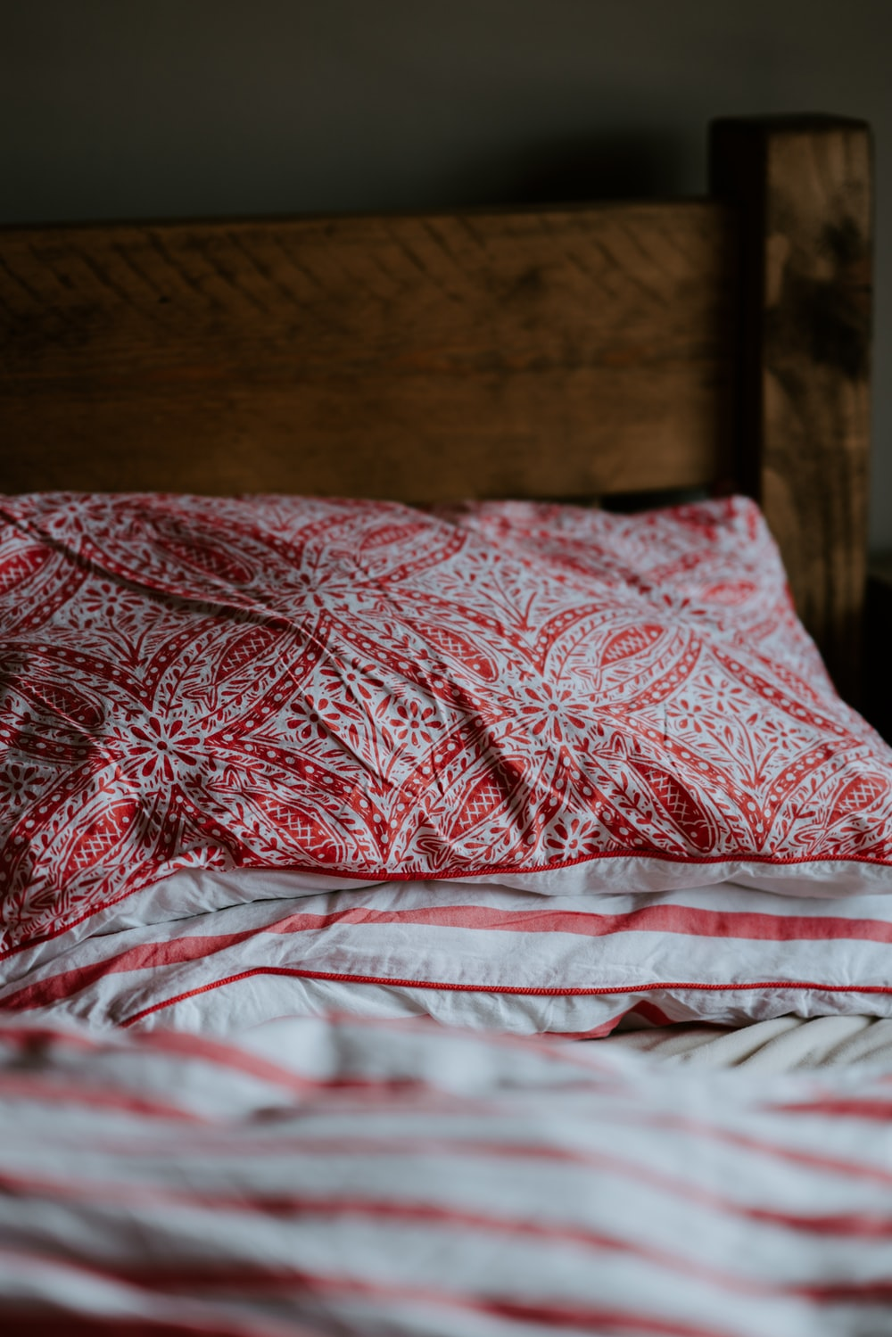 red and gray floral pillow on bedding