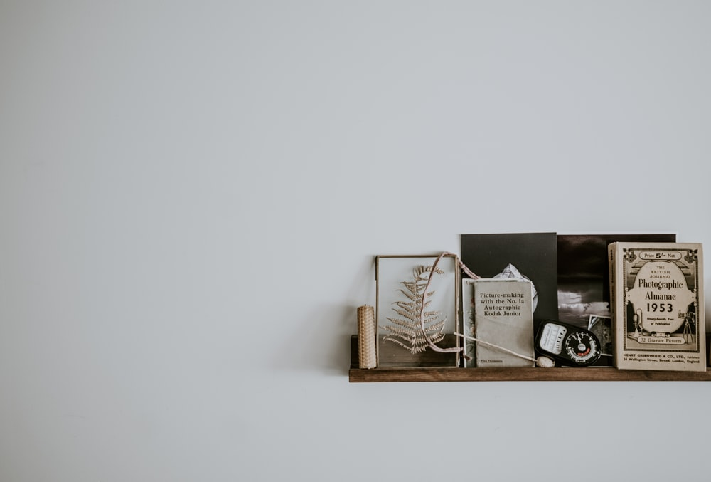 brown wooden floating shelf on white wall