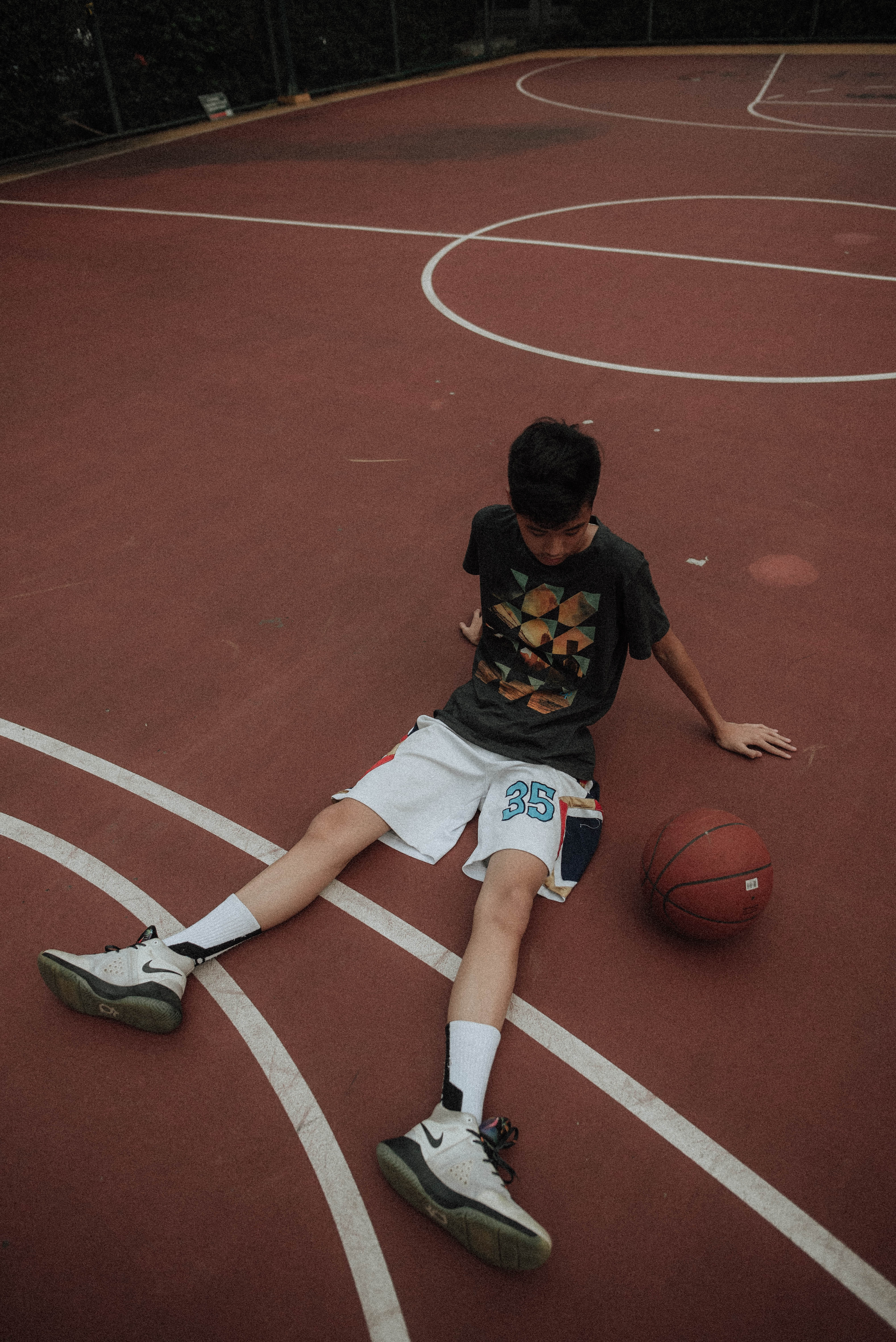 man lying on basketball court looking to basketball