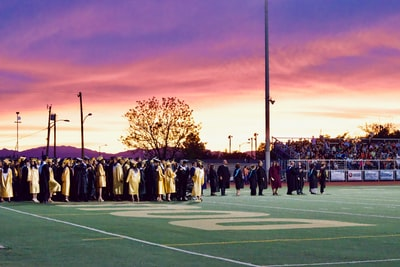 graduates gathered on football field commencement zoom background