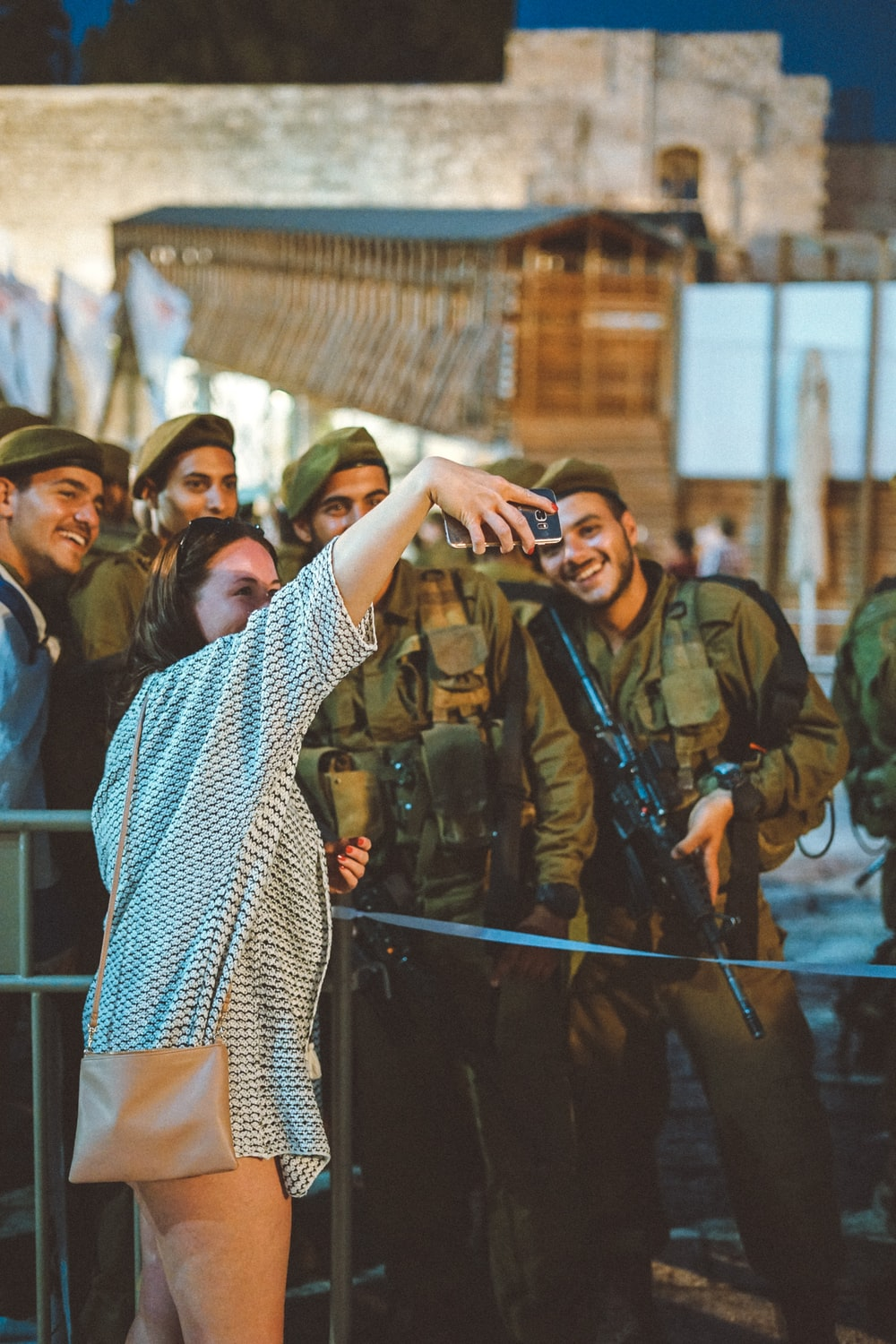 woman taking groupie picture with four militarys