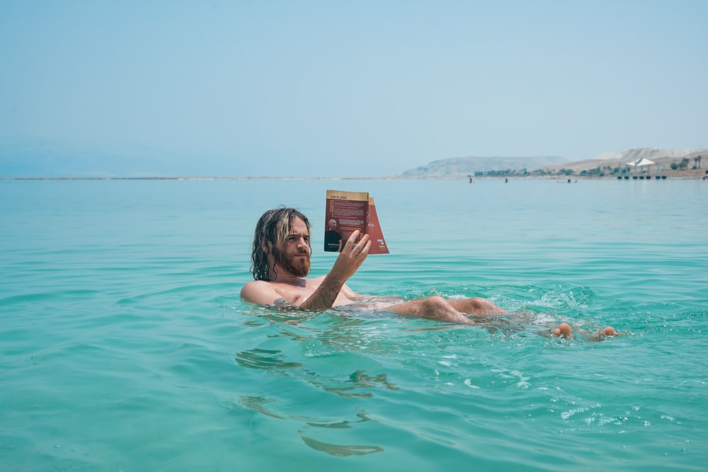 man floating on body of water while reading book