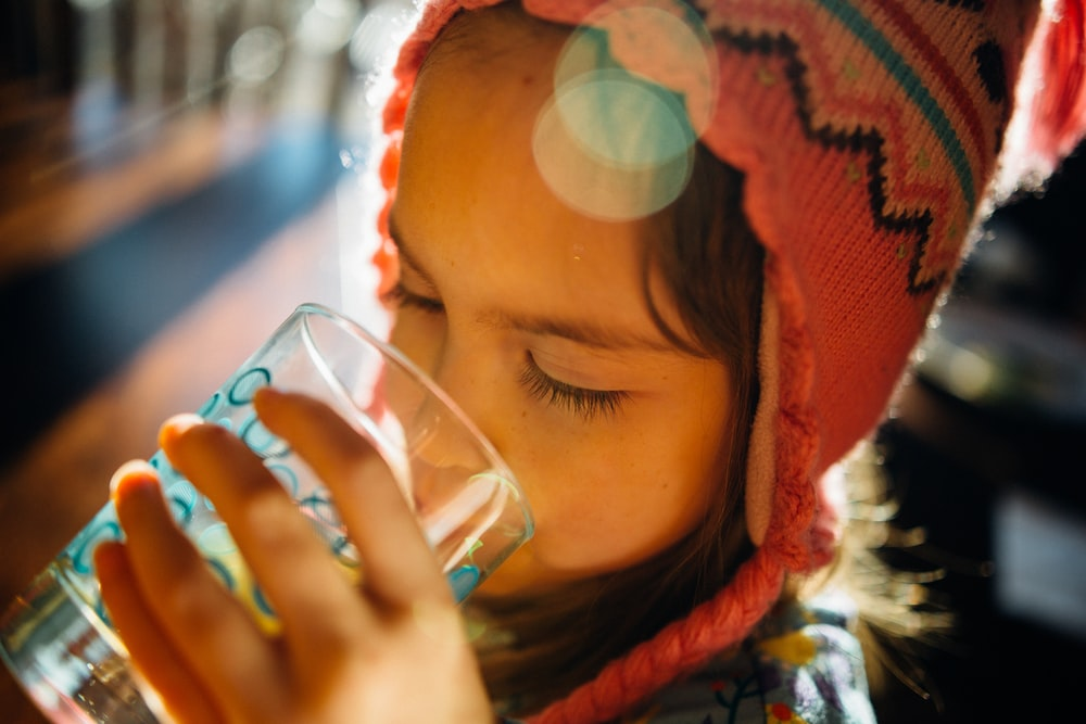selective focus photography of girl drinking water