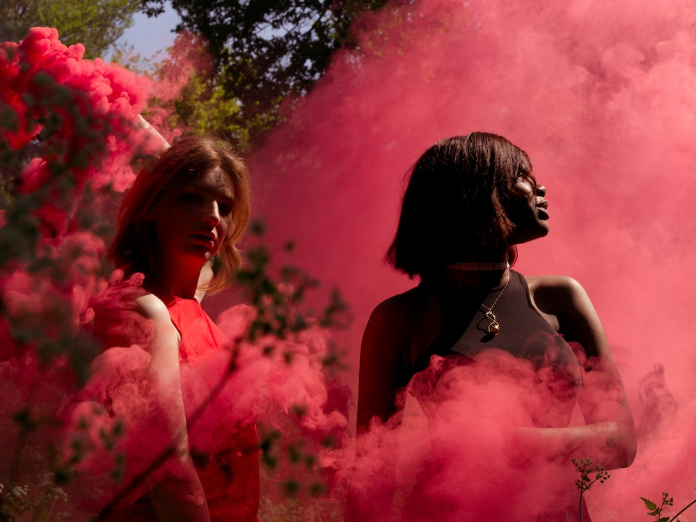 two women covered in red smoke