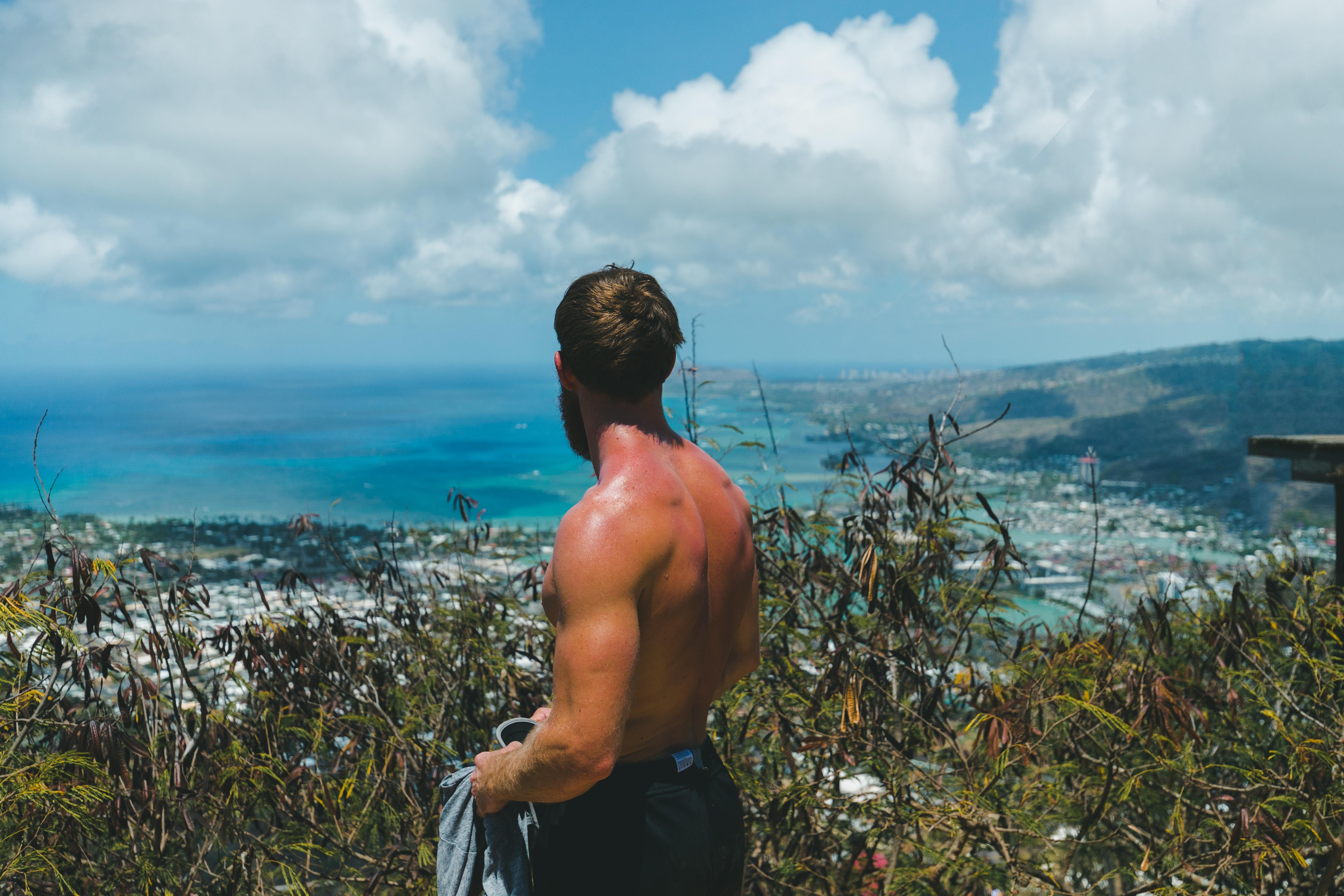 topless man facing sea horizon
