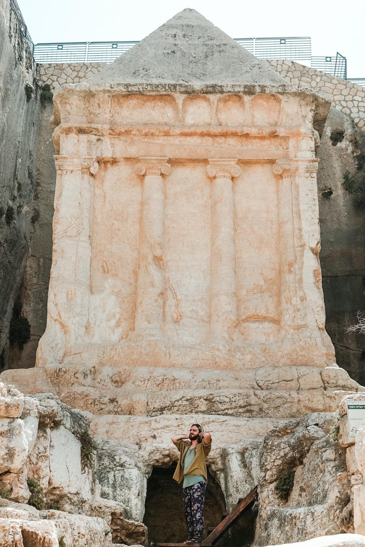 man standing near rock sculpture