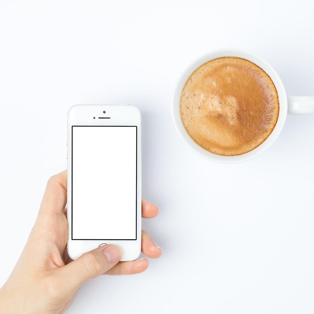 person silver iPhone 5s beside white ceramic mug