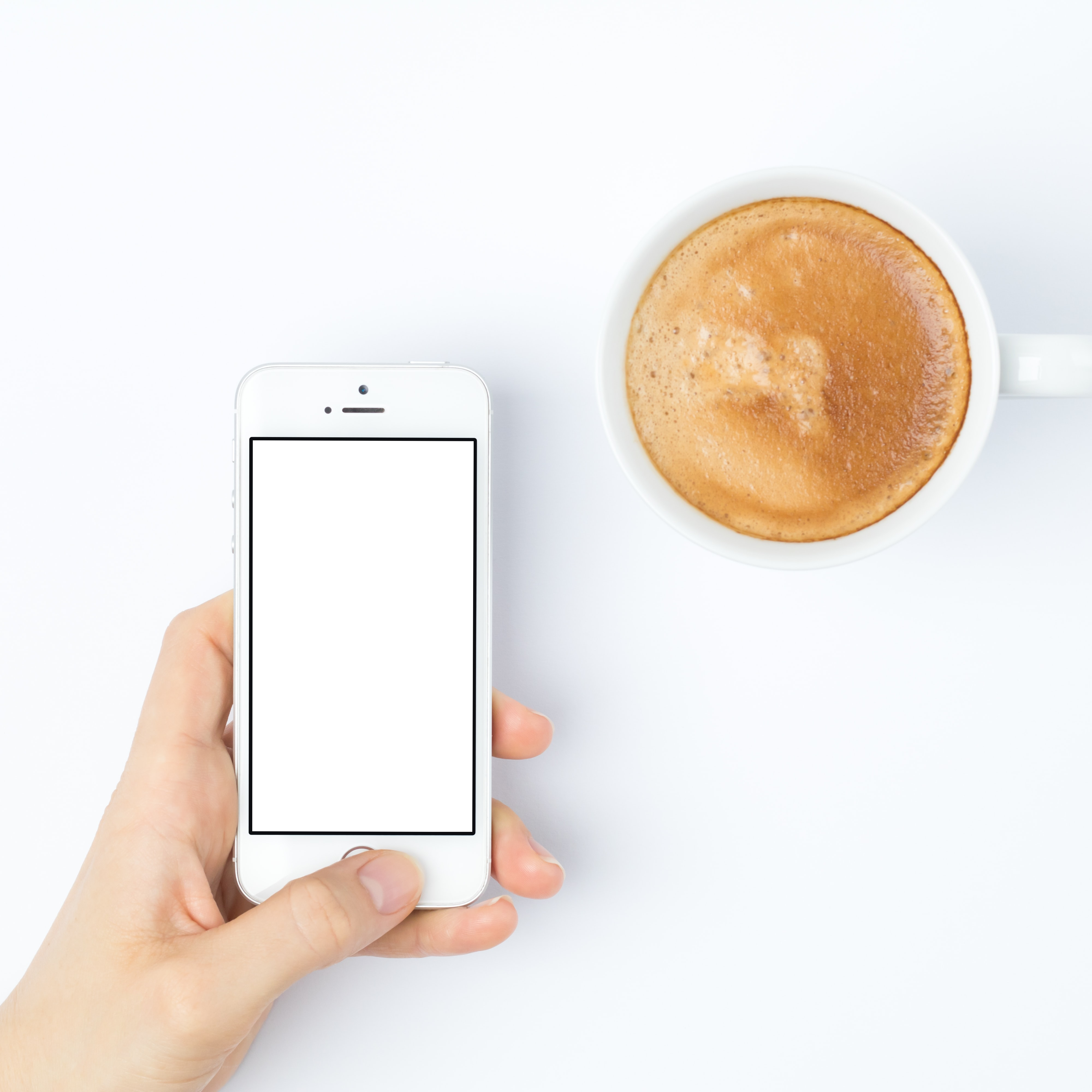 person silver iPhone 5s beside white ceramic mug