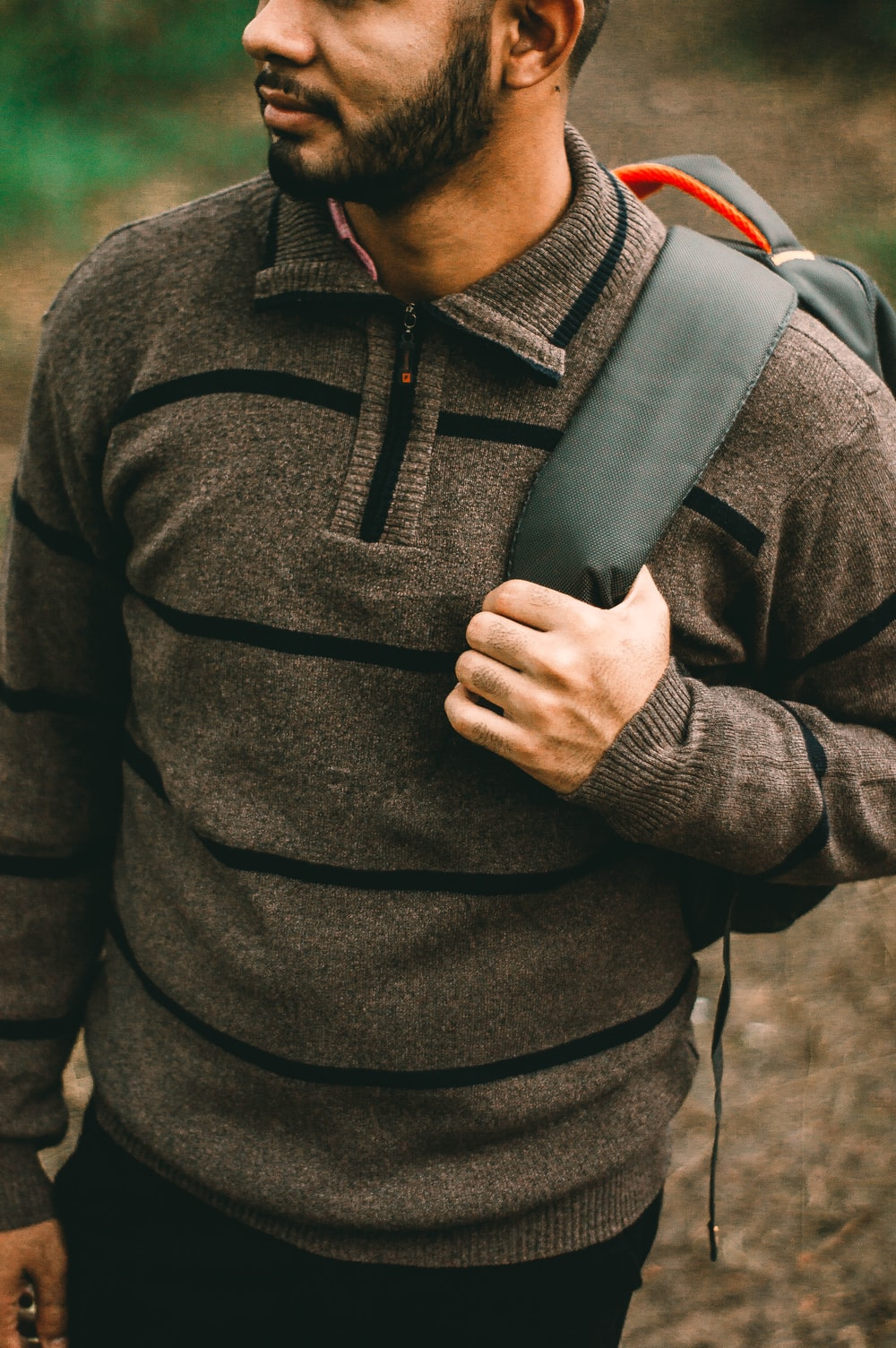 shallow focus photography of man holding of his backpack strap