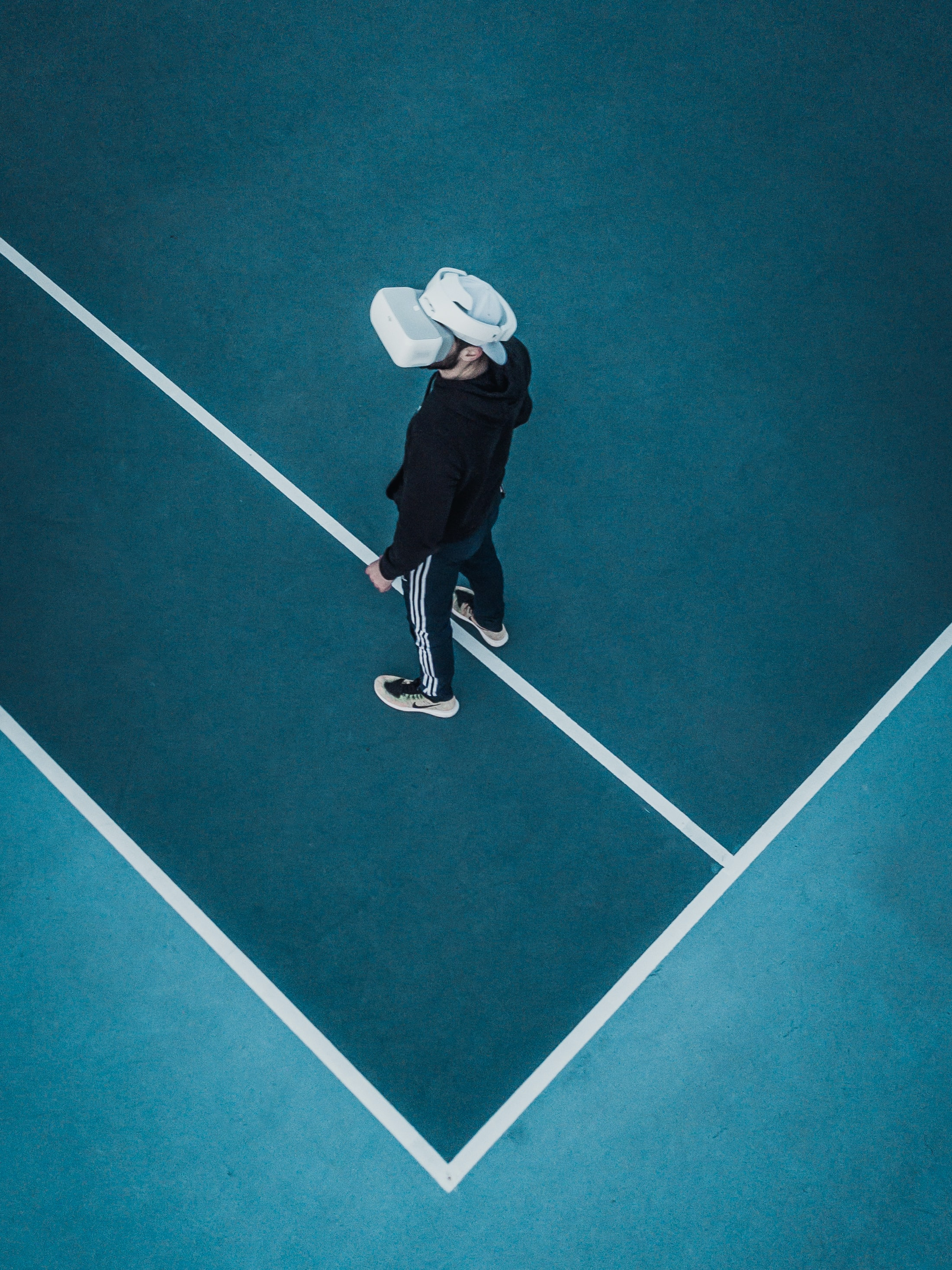 man in track suit wearing VR headset standing on tennis court