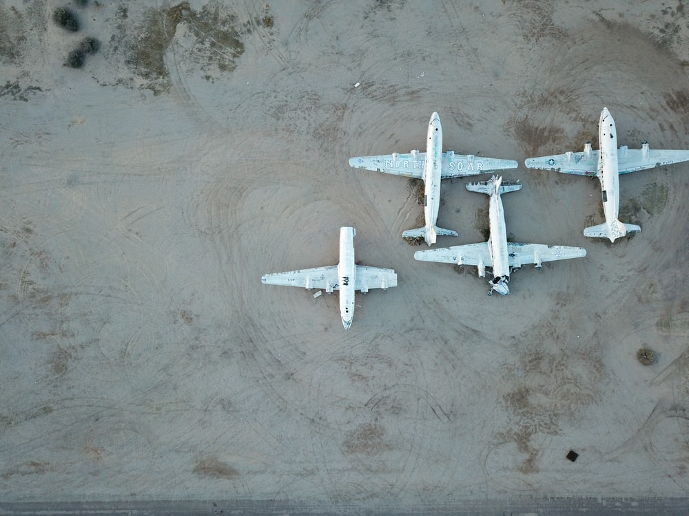 three white airplanes on grey surface