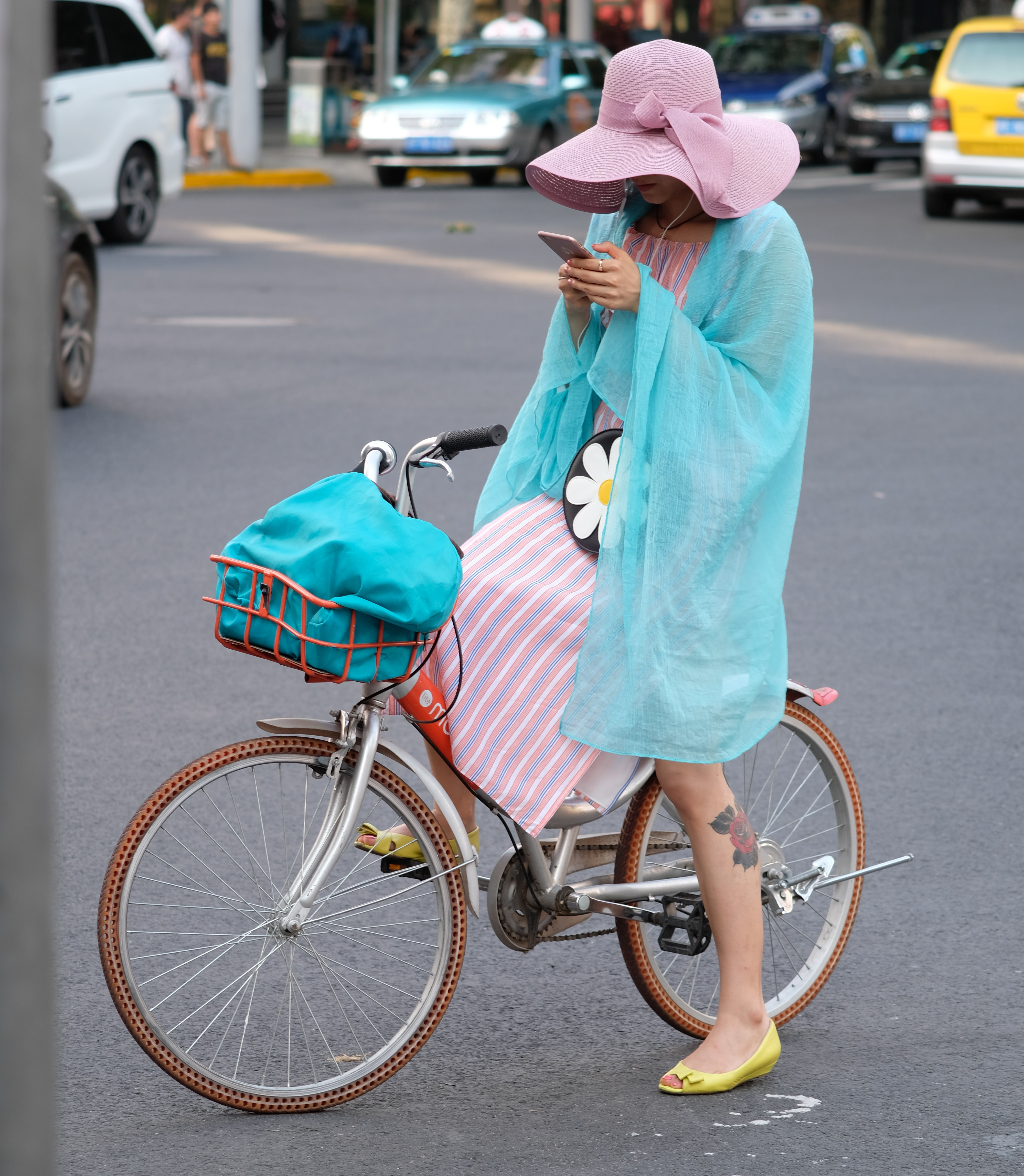 woman riding red bike stop center of road holding smartphone