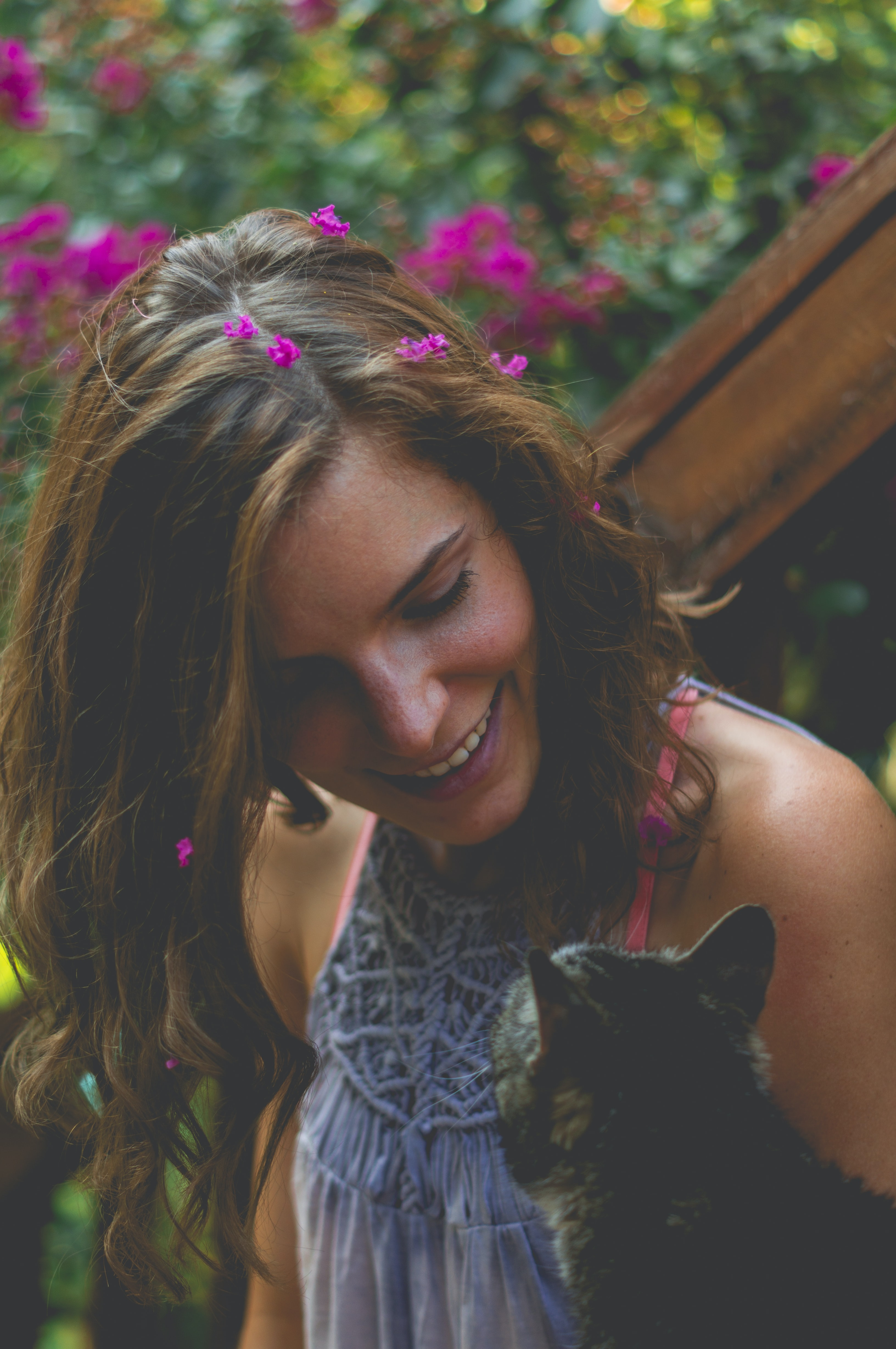 smiling woman looking at brown tabby cat