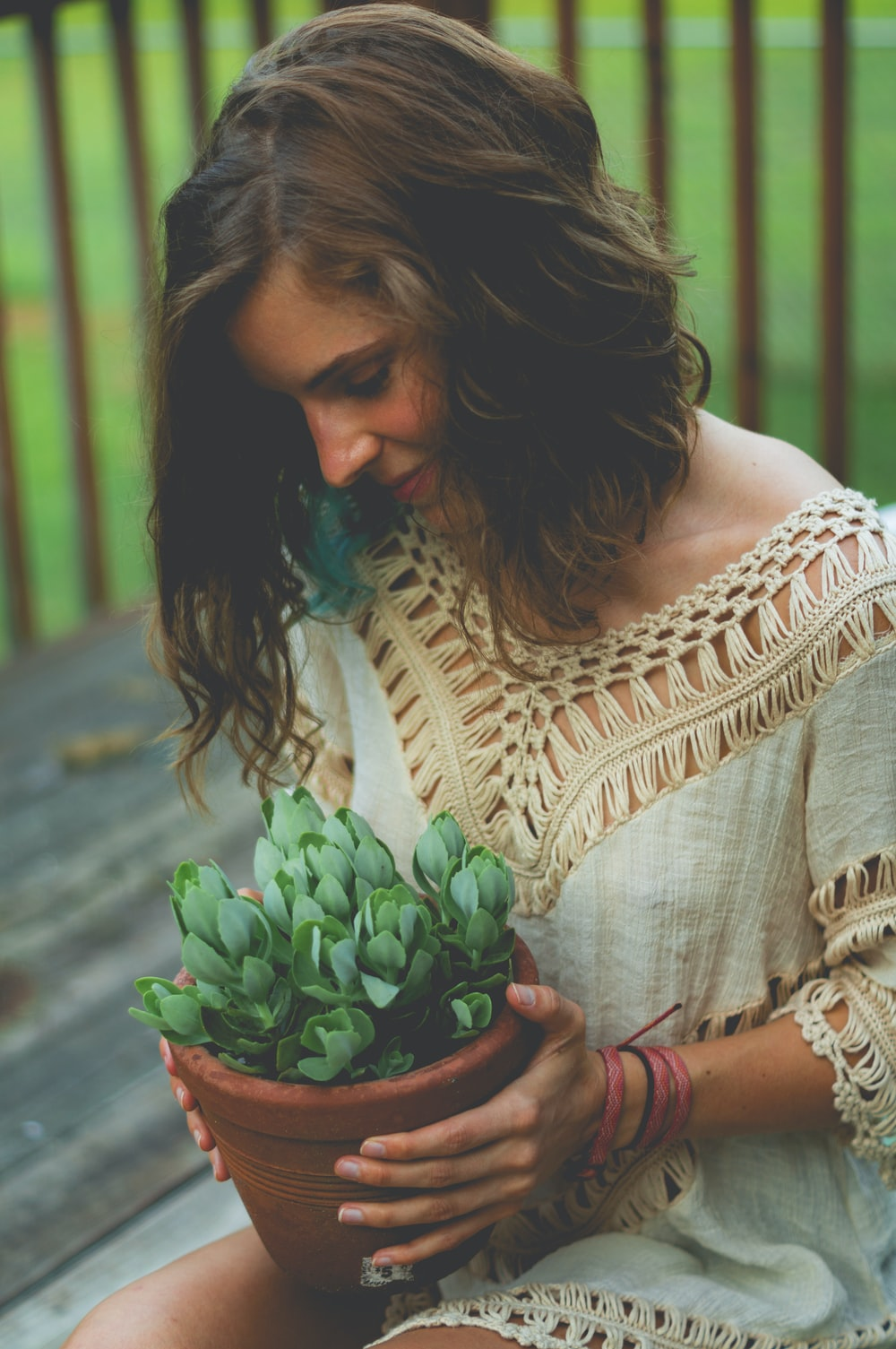 woman sitting while holding pot of succulent plants