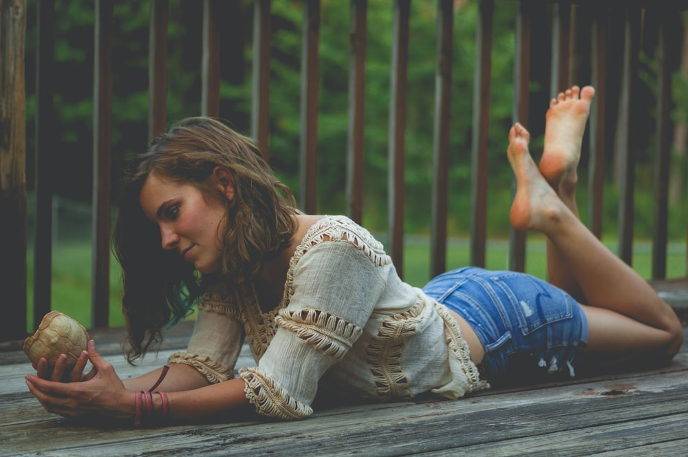 woman plank on wooden floor while holding shell
