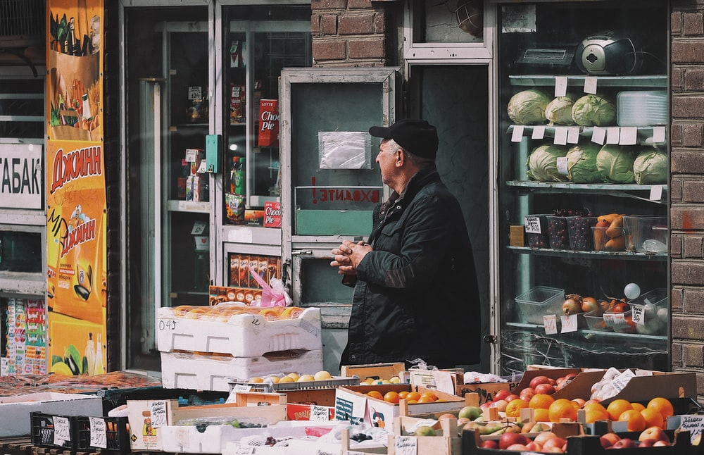 man standing on vegetable stand