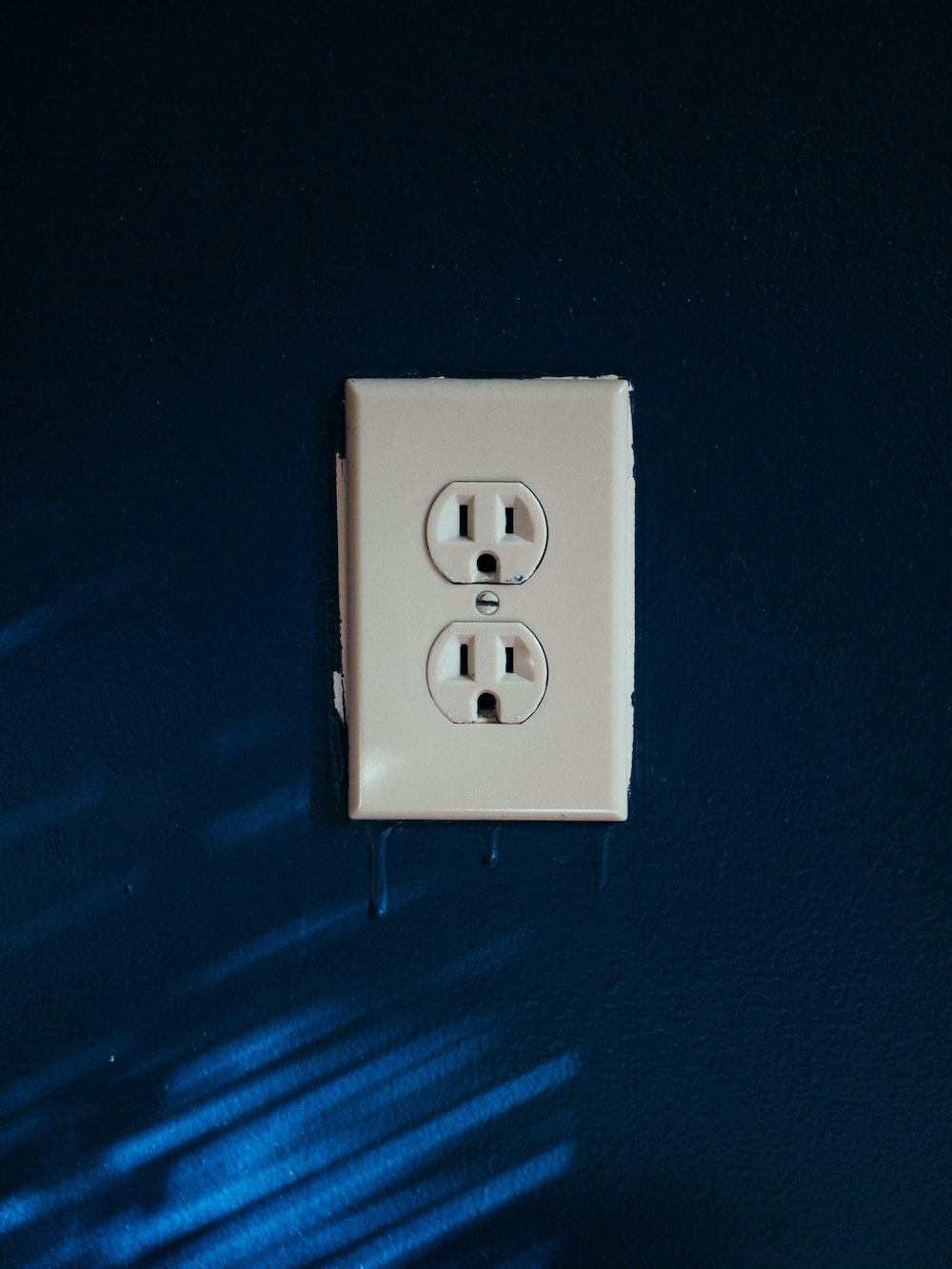 white 2-slot plug mounted on blue wall