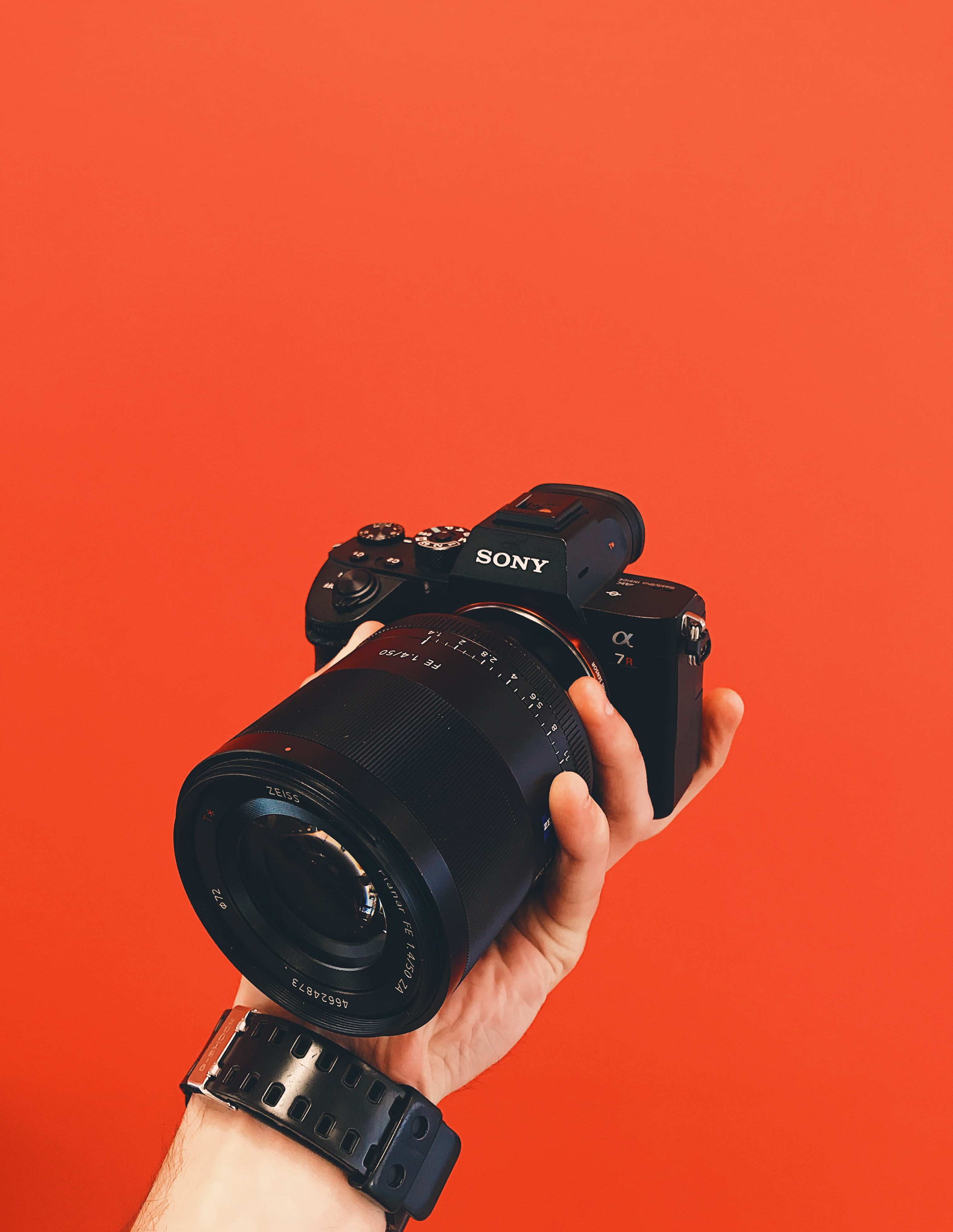 person holding black Sony Alpha DSLR camera