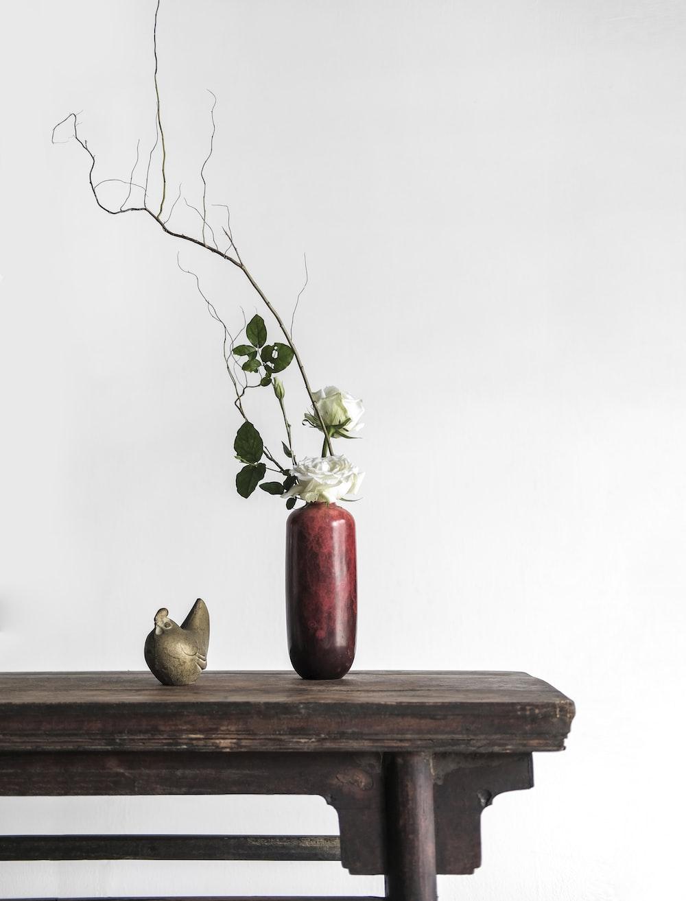 white roses in red ceramic vase