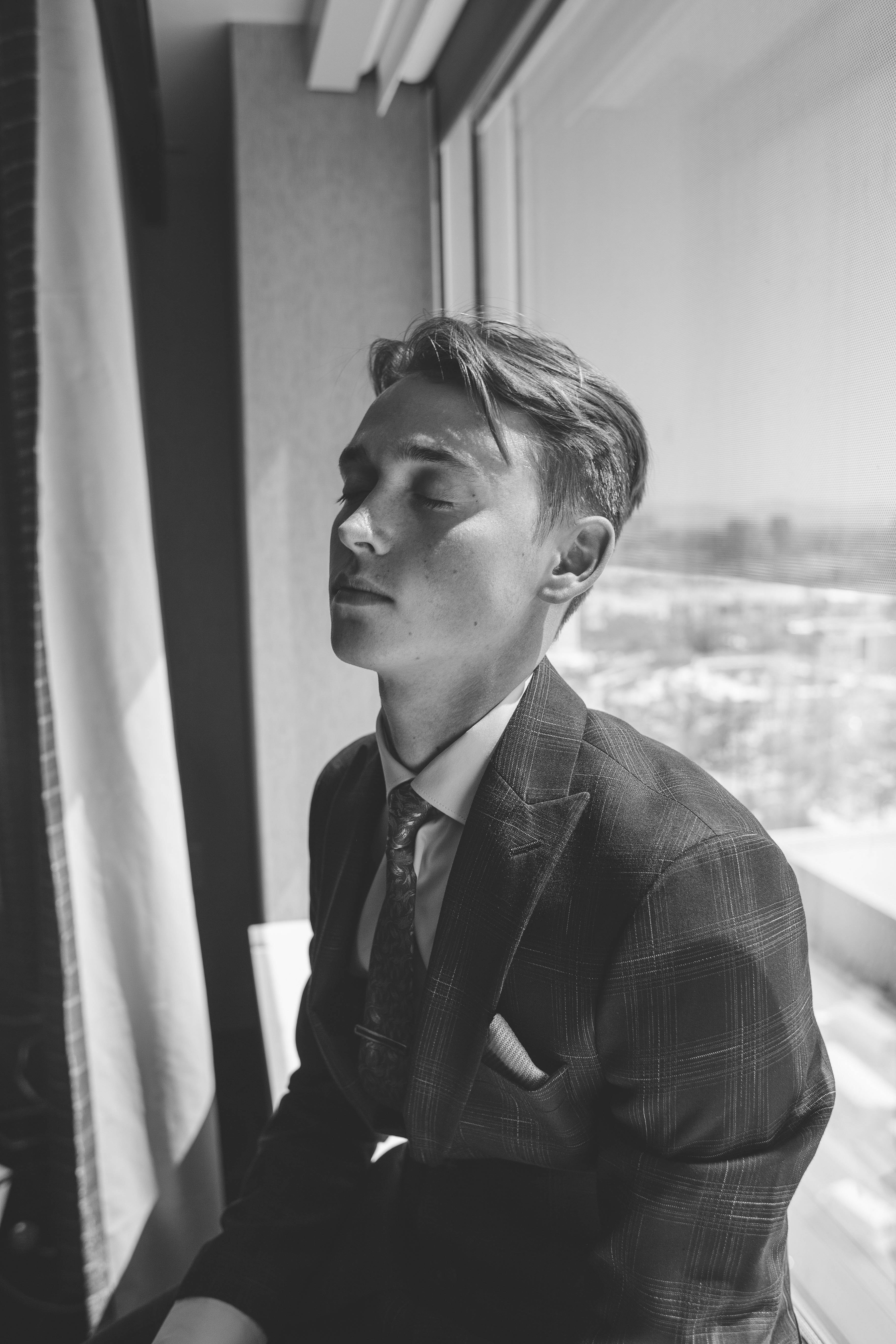 grayscale photo of man in peaked suit jacket sitting beside glass window
