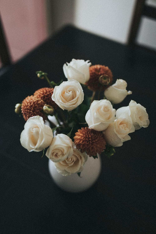white and orange flower arrangement in white ceramic vase on table