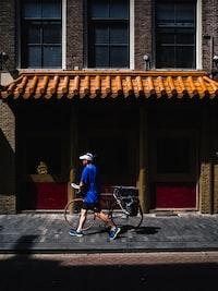 man walking while holding road bike