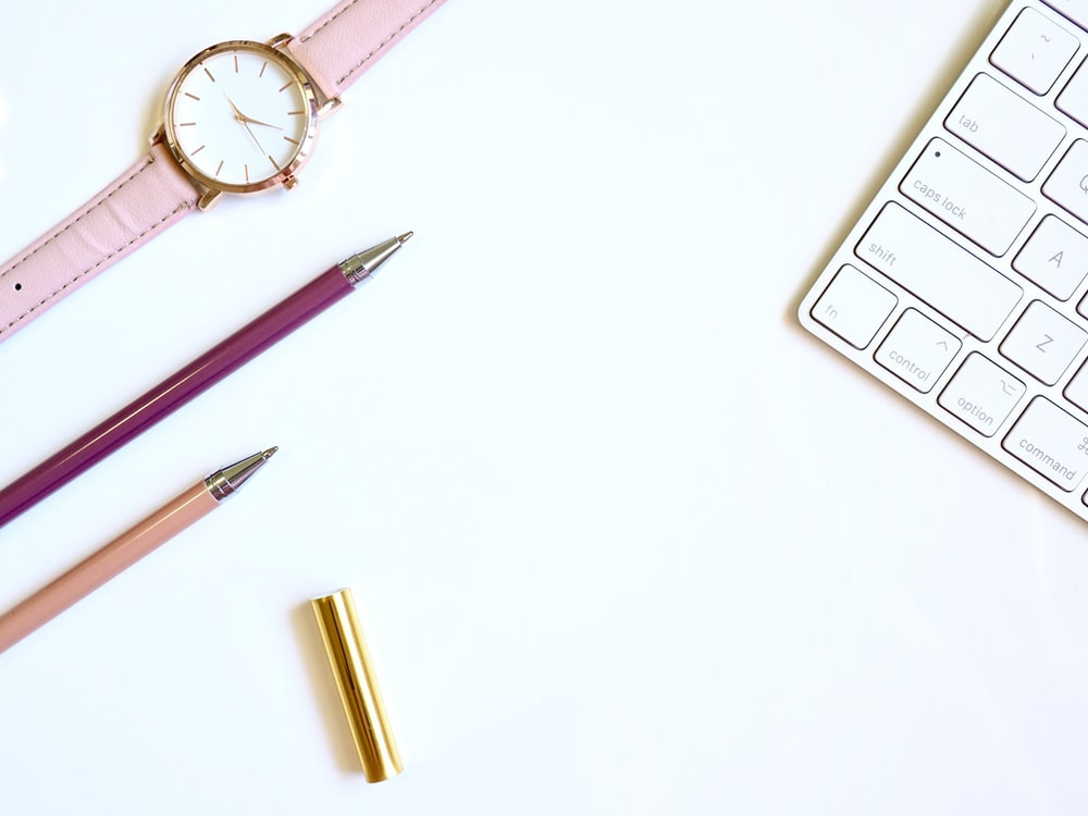 pink pen on table with round gold-colored analog watch