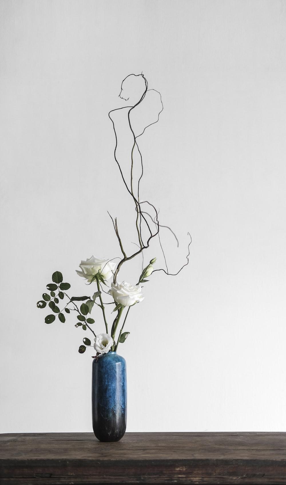 white flowers in blue vase
