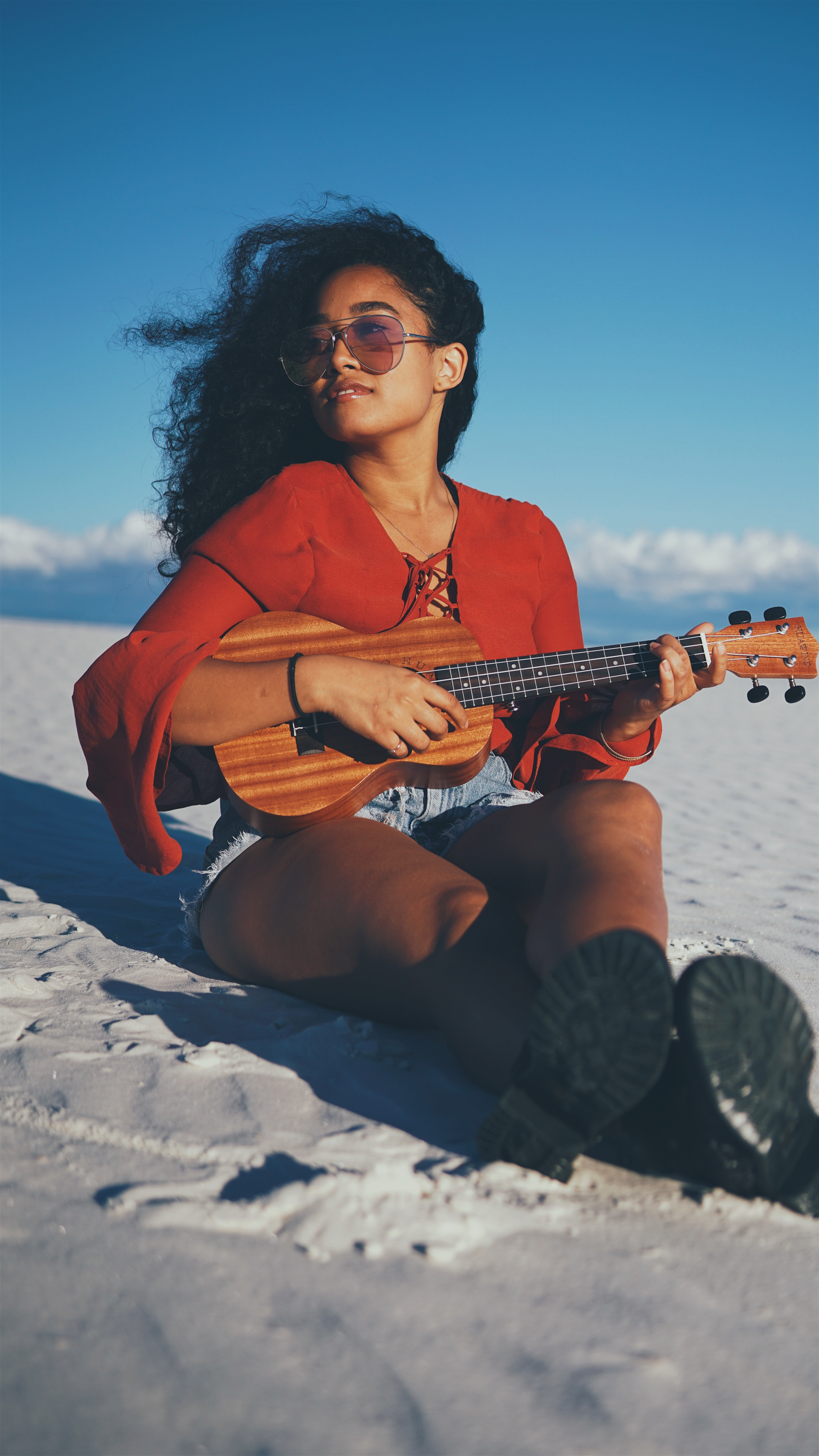 woman playing ukalele while sitting on gray sand