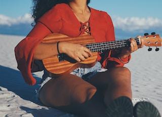 woman playing ukalele while sitting on gray sand