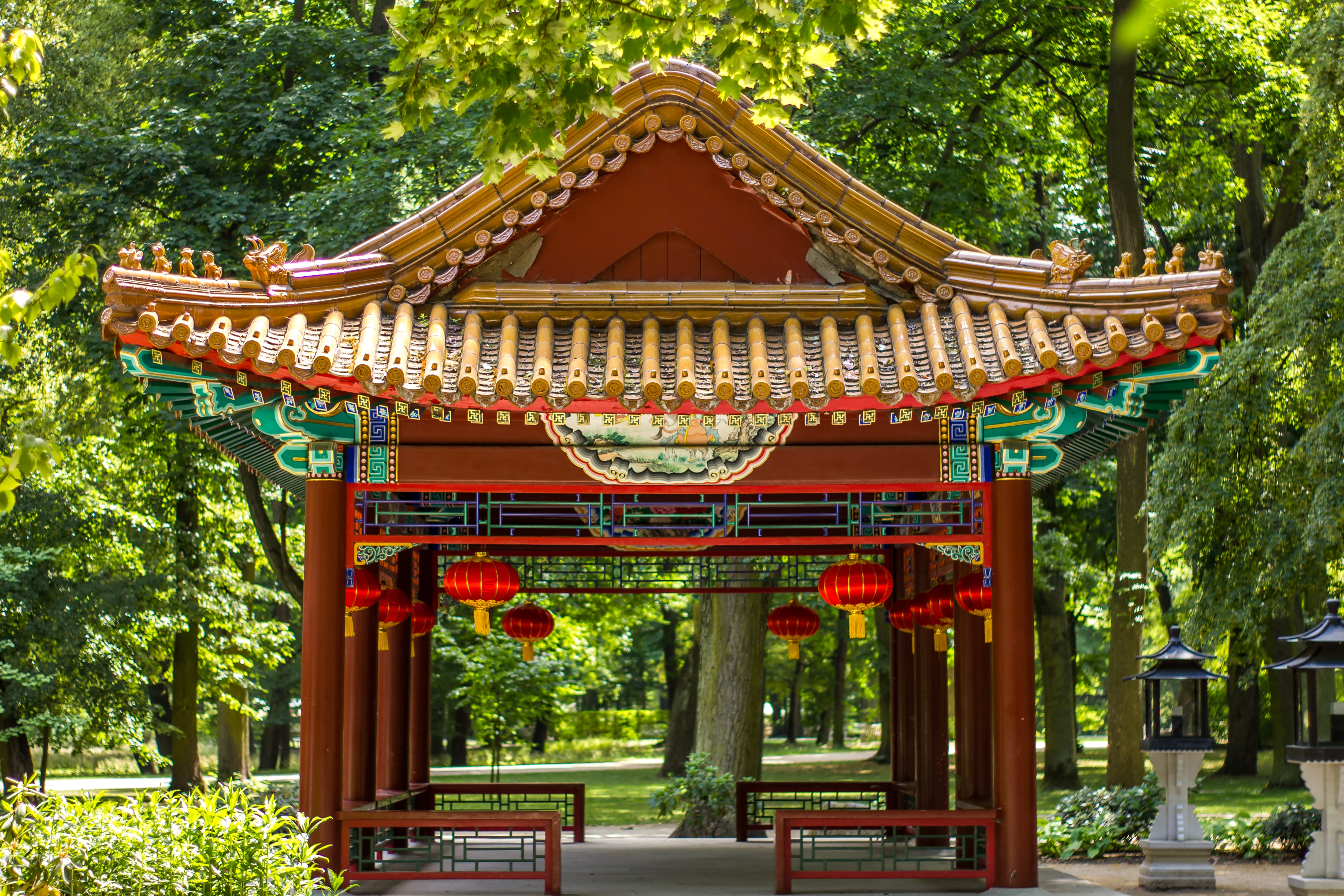 photo of red gazebo surrounded by green leafed trees