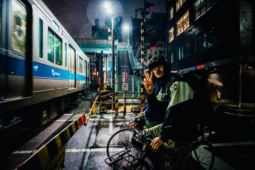 man riding bike near gray running train